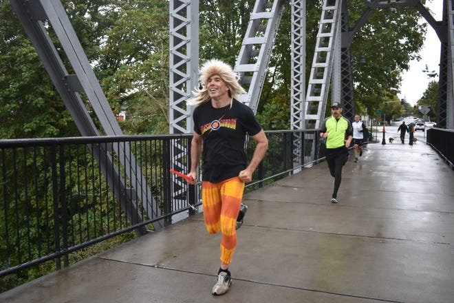 A runner dashes across the bridge during the first leg of the River 2 Ridge Relay.