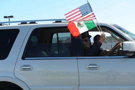El supervisor del condado de Monterey Simón Salinas ondea dos banderas durante el desfile de El Grito en Salinas.