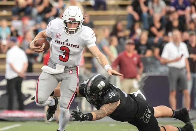 South Dakota quarterback Austin Simmons  (3) attempts to break free from being sacked by Weber State's Jayden Palauni (50) in the first half of play Saturday, Sept. 15, 2018, at Stewart Stadium in Ogden. Matt Herp/Standard-Examiner