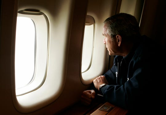 President George W. Bush looks out the window of Air Force One inspecting damage from Hurricane Katrina while flying over New Orleans en route back to the White House on Aug, 31, 2005.