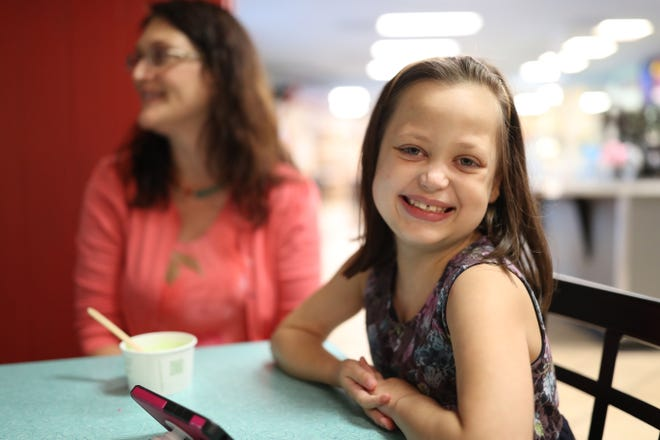 Chloe Novak, 8, was born with a heart defect that caused it to grow too large for her body. The day after her second birthday, she received a heart transplant. Doctors told her parents that she had a slim chance of surviving birth, but she has defied the odds ever since. Chloe's mother, Carolyn, sits behind her at Lofty Pursuits on Aug. 29, 2018.