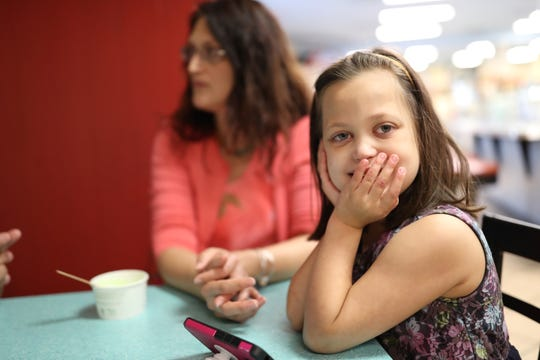Chloe Novak, 8, was born with a heart defect that caused it too grow to large for her body. The day after her second birthday, she received a heart transplant. Doctors told her parents that she had a slim chance of surviving birth, but she has defied the odds ever since. Chloe's mother, Carolyn, sits behind her at Lofty Pursuits on Aug. 29, 2018.