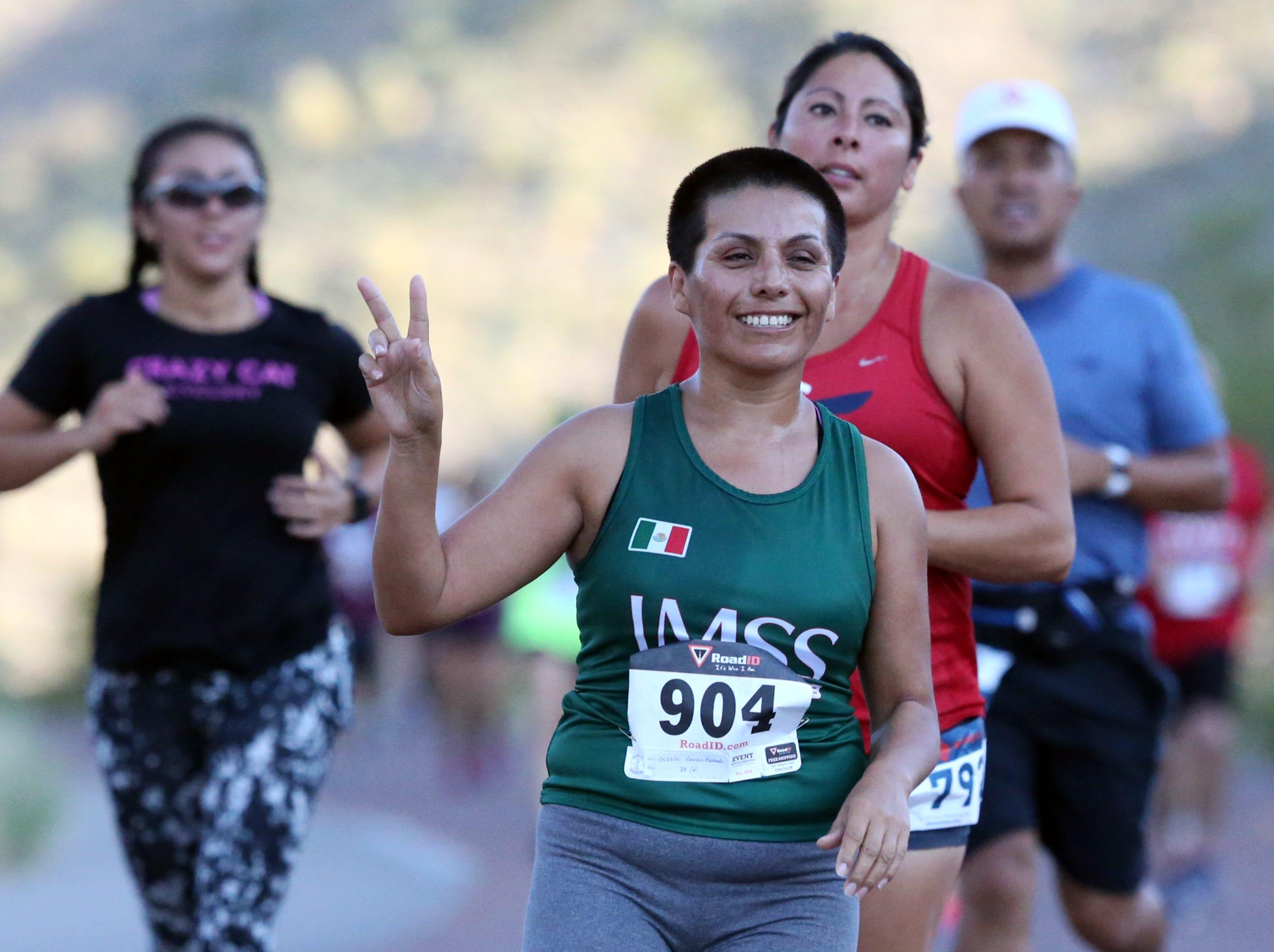 Gisela Garcia, center, runs in the 7th annual McKelligon Canyon Challege Sunday.