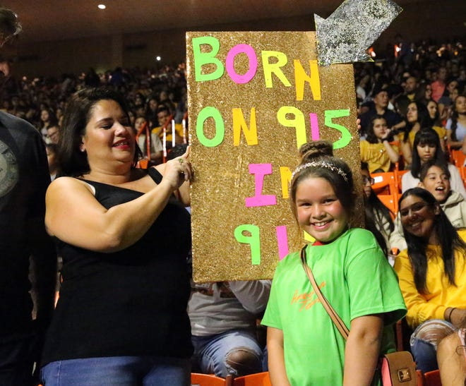 Georgina Williams holds a sign for her daughter, Elizabeth Lexie Panahi 10, who was celebrating her birthday at the Khialid concert Saturday in the Don Haskins Center.