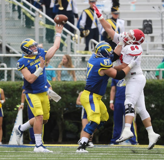 Delaware's Pat Kehoe throws past lineman Connor Lutz and Cornell's Michael Gillooley in the second quarter at Delaware Stadium Saturday.