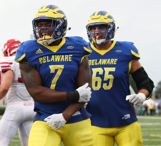 Delaware's Kani Kane celebrates as he is joined by teammate Noah Beh after scoring on a three-yard run in the fourth quarter of the Blue Hens' 27-10 win at Delaware Stadium Saturday.