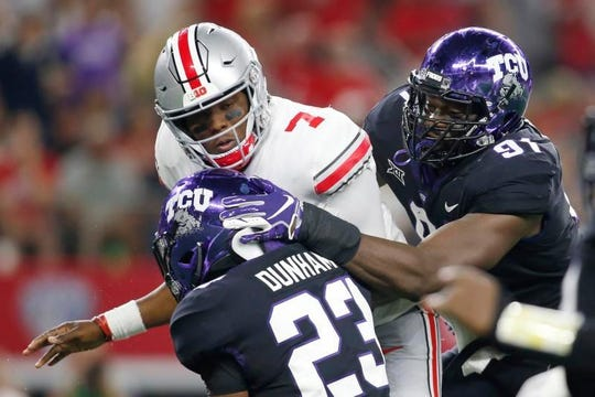 Buckeyes quarterback Dwayne Haskins (7) is hit after throwing a pass is in the second quarter by TCU Horned Frogs linebacker Alec Dunham (23) and defensive end L.J. Collier (91) at AT&T Stadium.