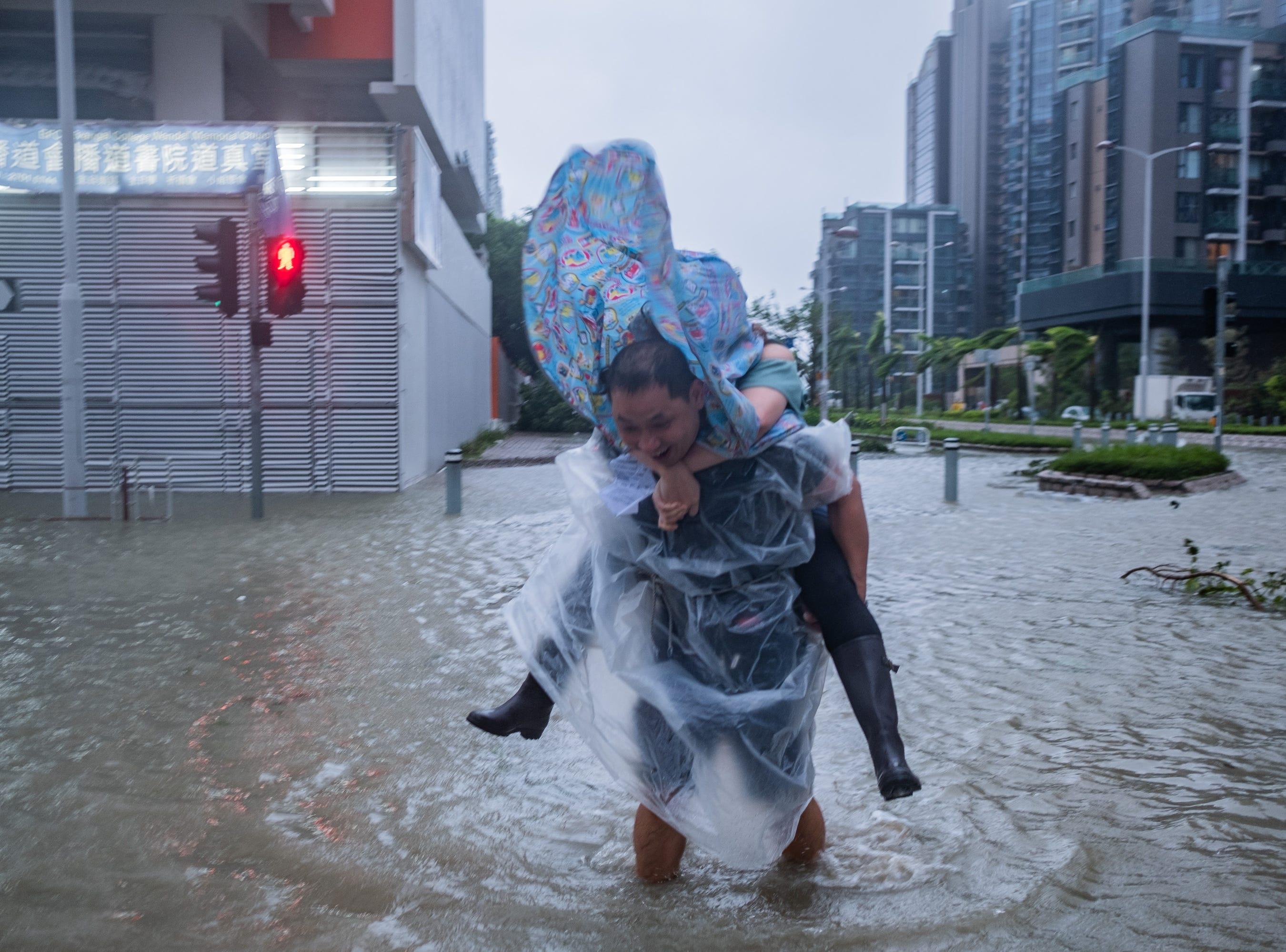 A man carrying a woman cross a flooded road on Sept. 16, 2018 in Hong Kong, Hong Kong.