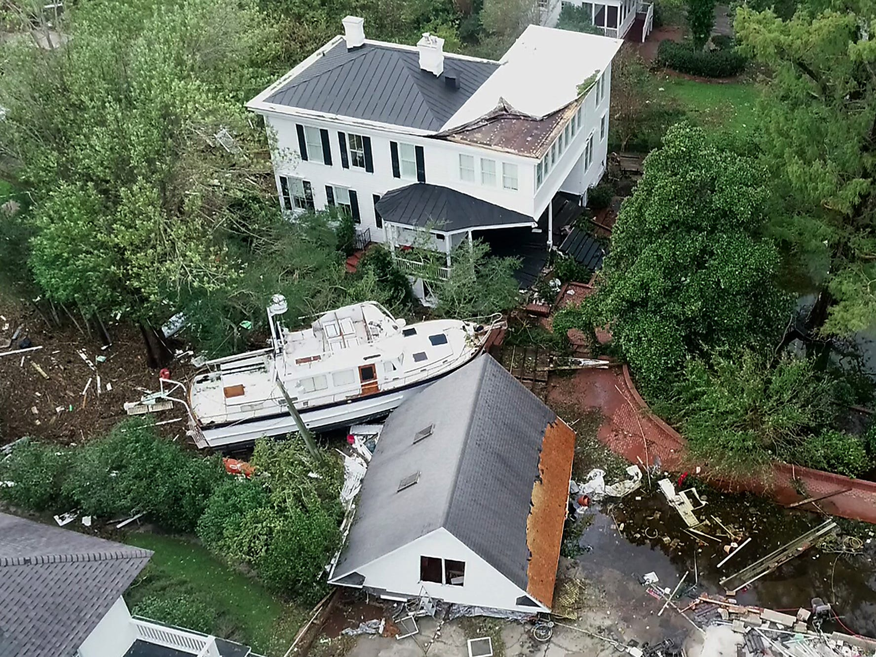 A yacht sits between two homes in the historic downtown neighborhood in New Bern, N.C. on Sunday morning on Sept. 16, 2018. A homeowner said the yacht drifted from across the river in Bridgeton.