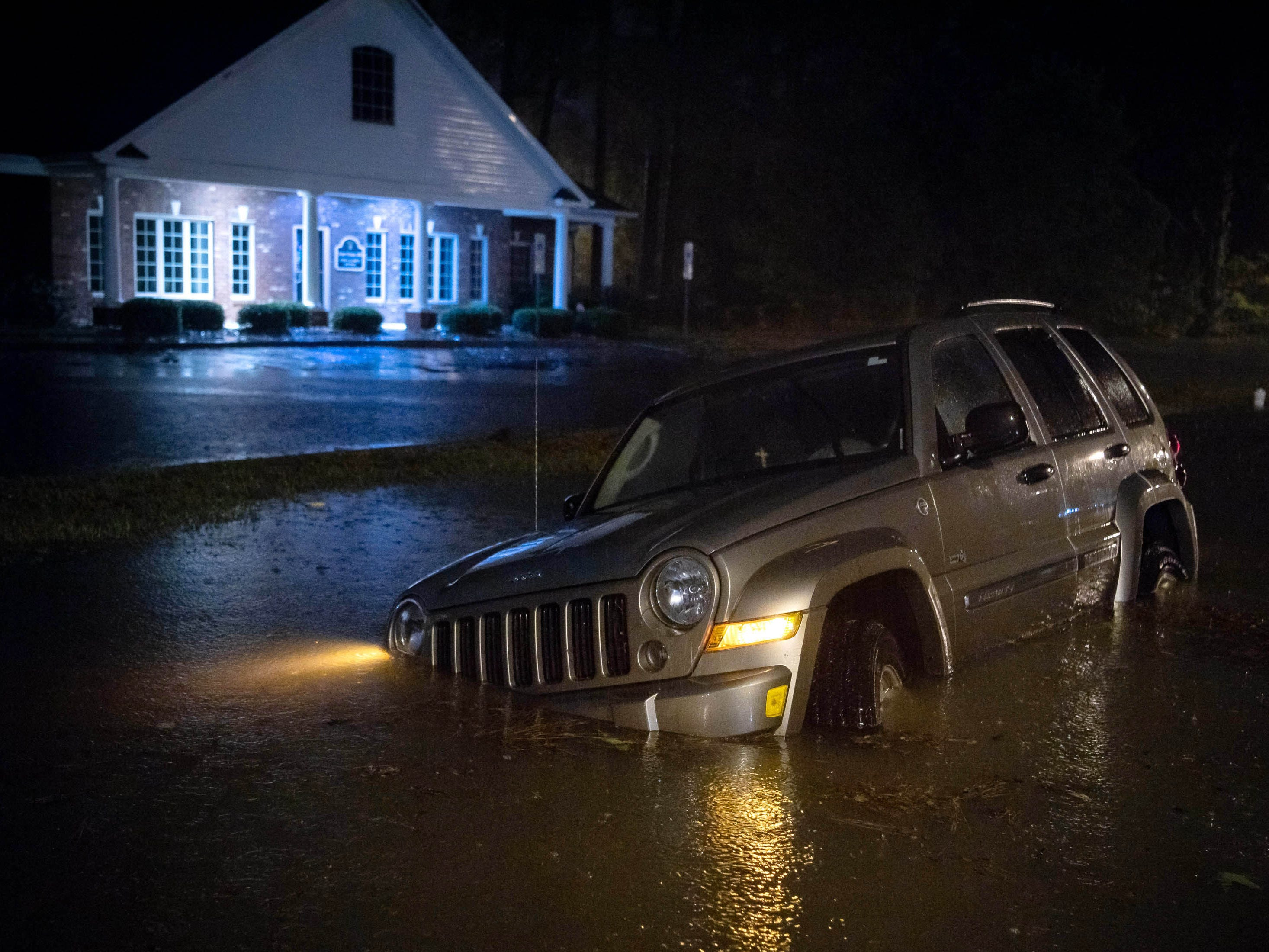 An abandoned SUV sits in a flooded neighborhood as rain from tropical storm Florence continues to fall on Lumberton, N.C., on Sept. 15, 2018.