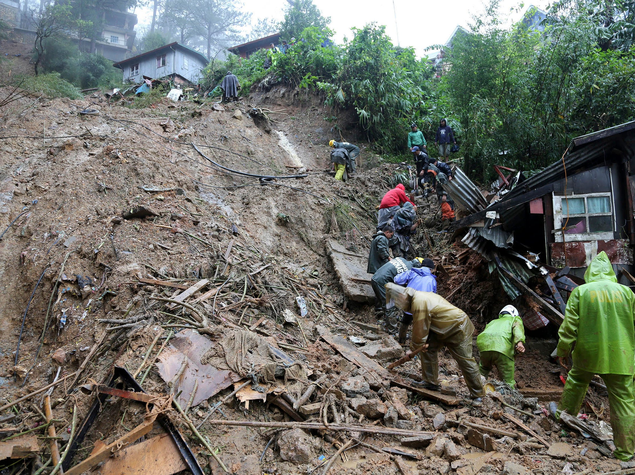 Rescuers and paramedics and volunteers conduct search and retrieval operation to locate the three missing persons who were buried due to landslide caused by typhoon Mangkhut at Balacbac, Baguio City, north of Manila, Philippines on Sept. 16, 2018.