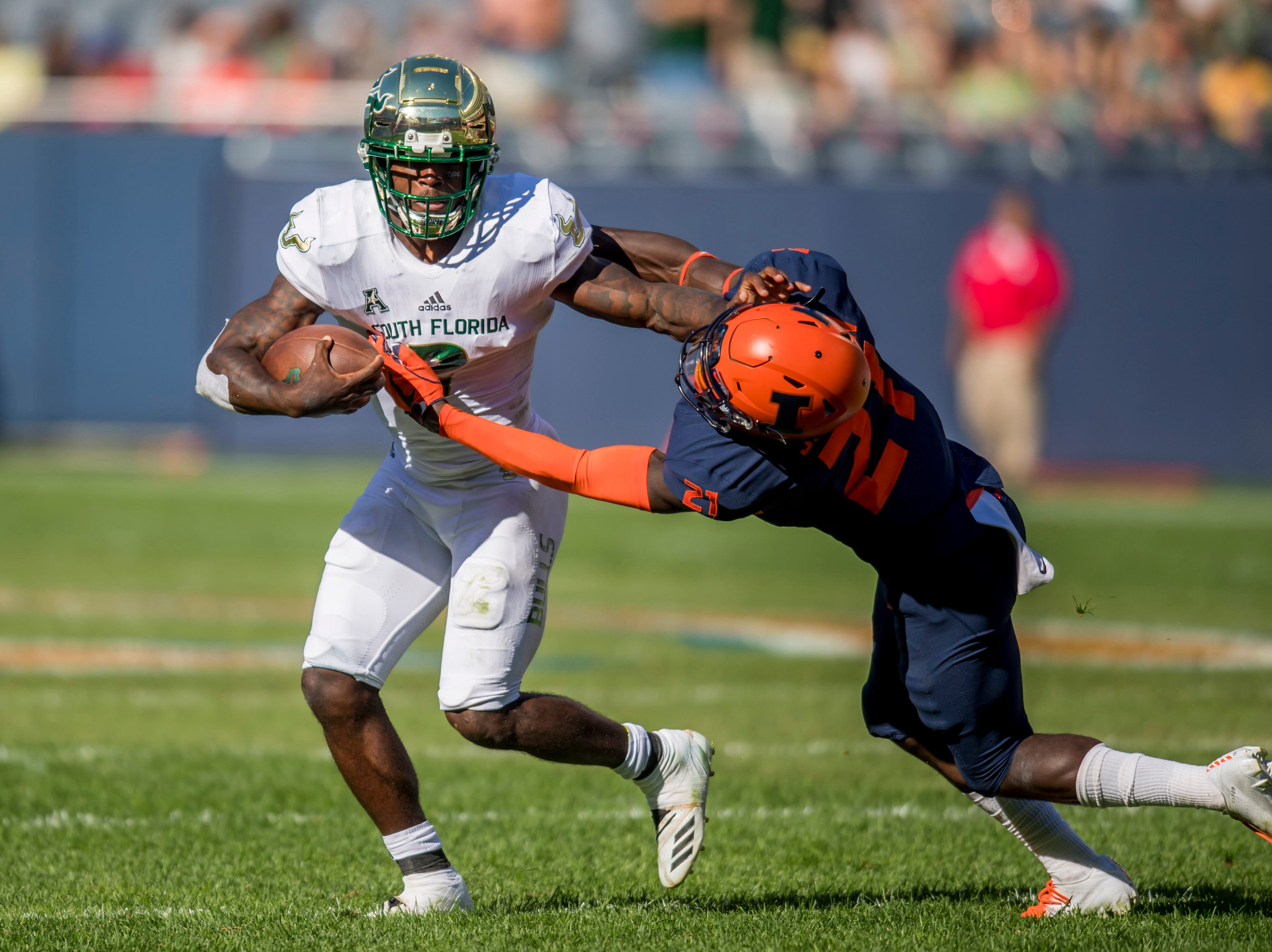 South Florida Bulls running back Jordan Cronkrite (2) stiff-arms Illinois Fighting Illini defensive back Jartavius Martin (21) during the first half at Soldier Field.
