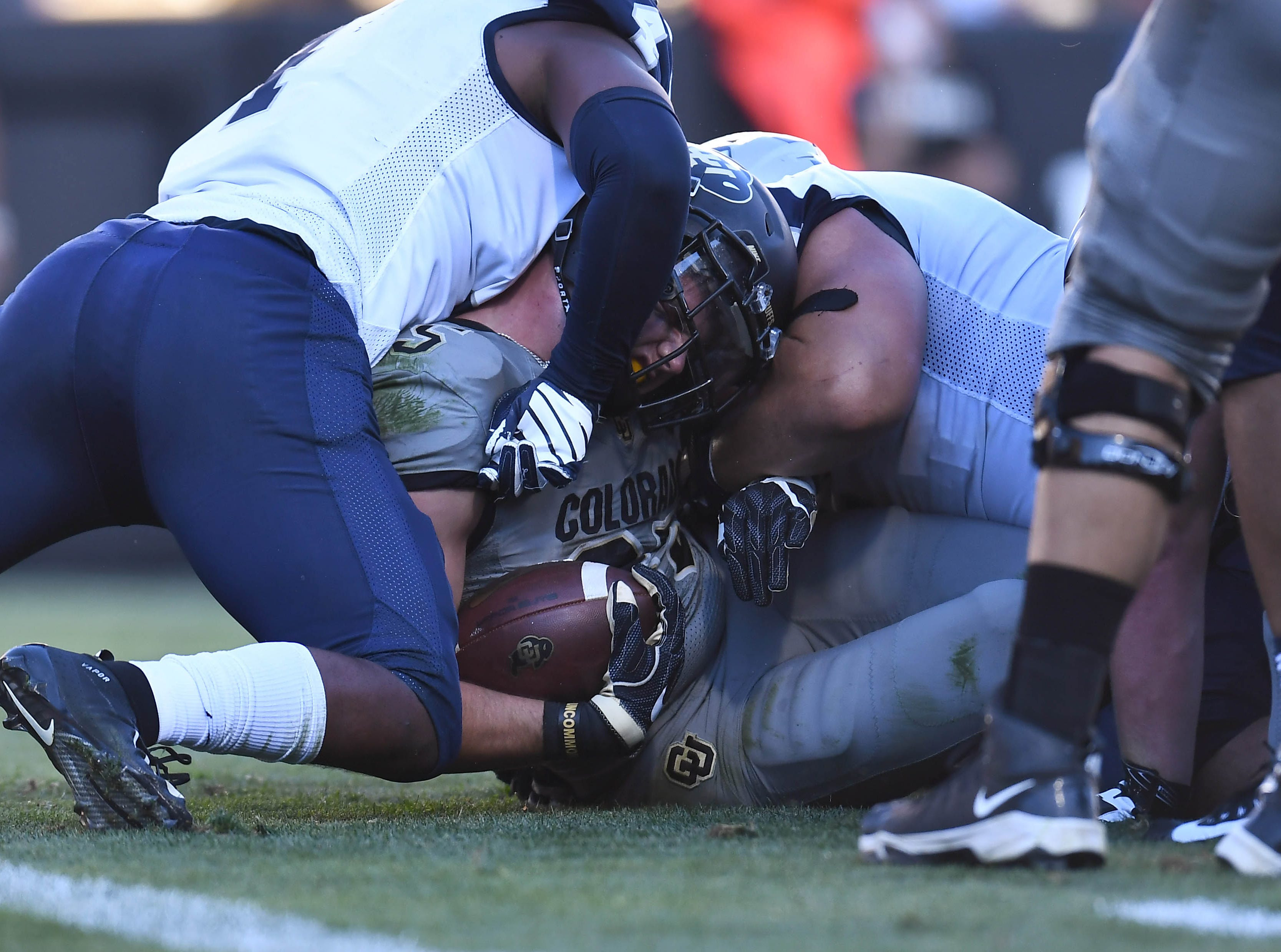 Colorado Buffaloes running back Travon McMillian (34) is tackled after a carry by New Hampshire Wildcats linebacker Quinlen Dean (4) in the second half of the game at Folsom Field.