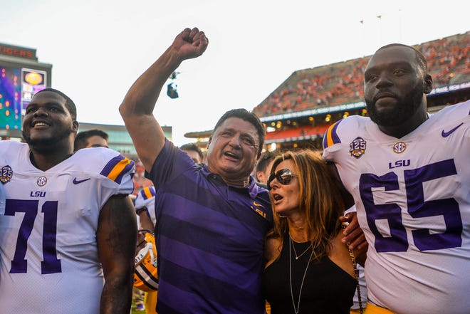 LSU coach Ed Orgeron celebrates with players and his wife Kelly, after defeating the Auburn at Jordan-Hare Stadium.