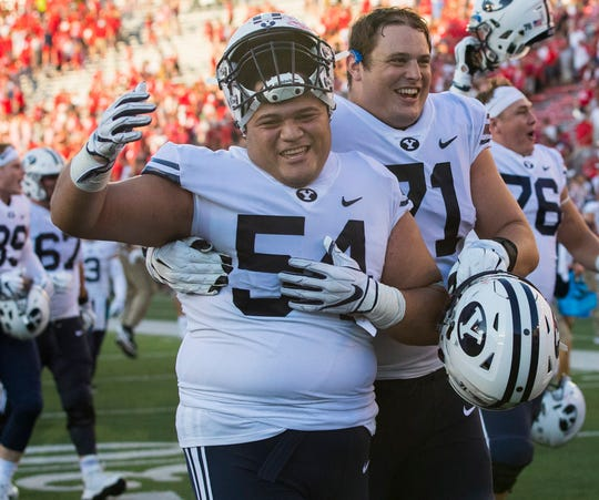 Brigham Young defensive lineman Merrill Taliauli (54) and offensive lineman Austin Hoyt celebrate after their team's win against Wisconsin.