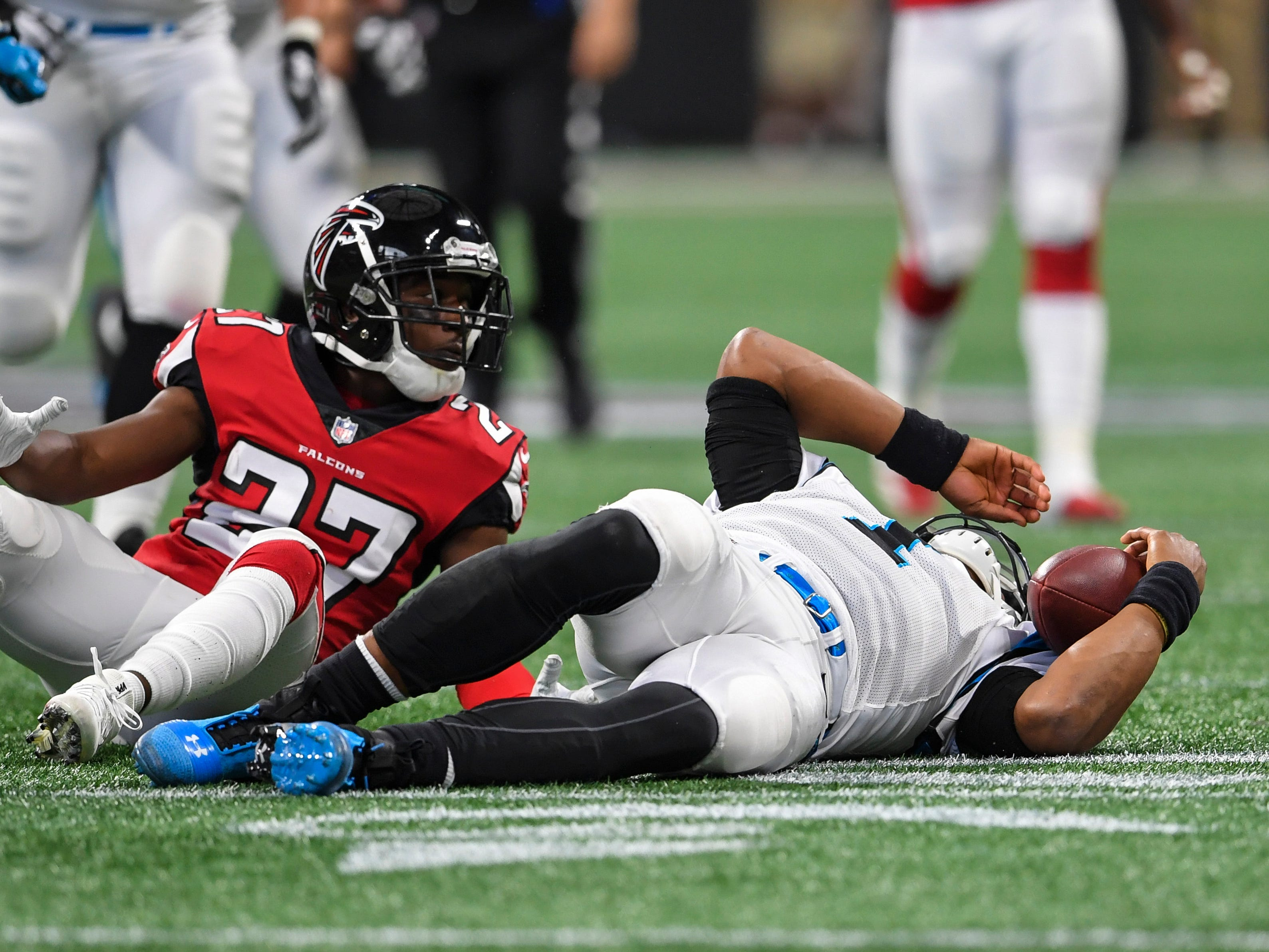 Carolina Panthers quarterback Cam Newton lays on the field after being hit in the head while sliding by Atlanta Falcons cornerback Damontae Kazee during the first half at Mercedes-Benz Stadium. Kazee was ejected for the hit.
