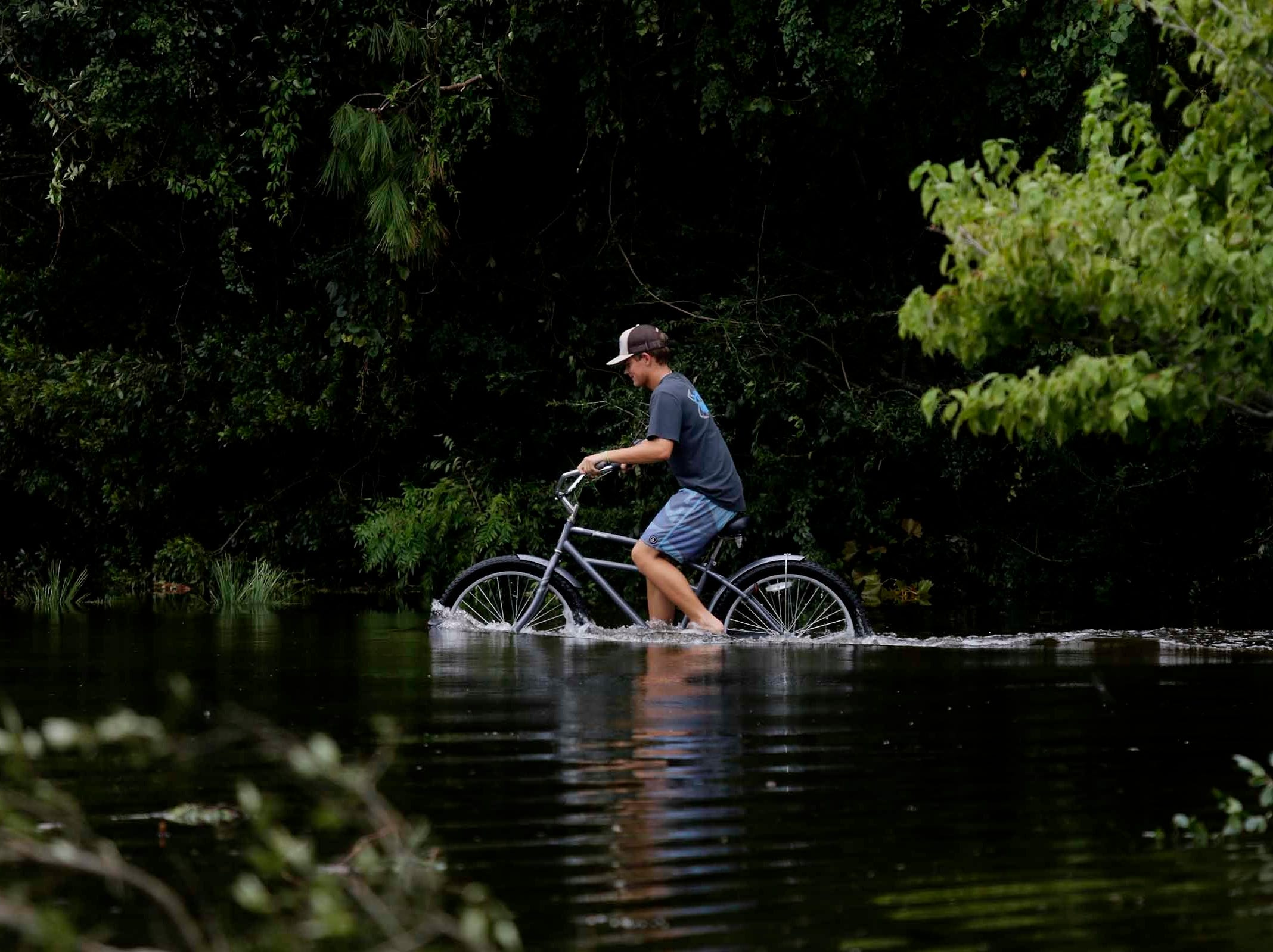 James Register rides his bike on flooded roads after Hurricane Florence hit Emerald Isle N.C.,Sunday, Sept. 16, 2018.