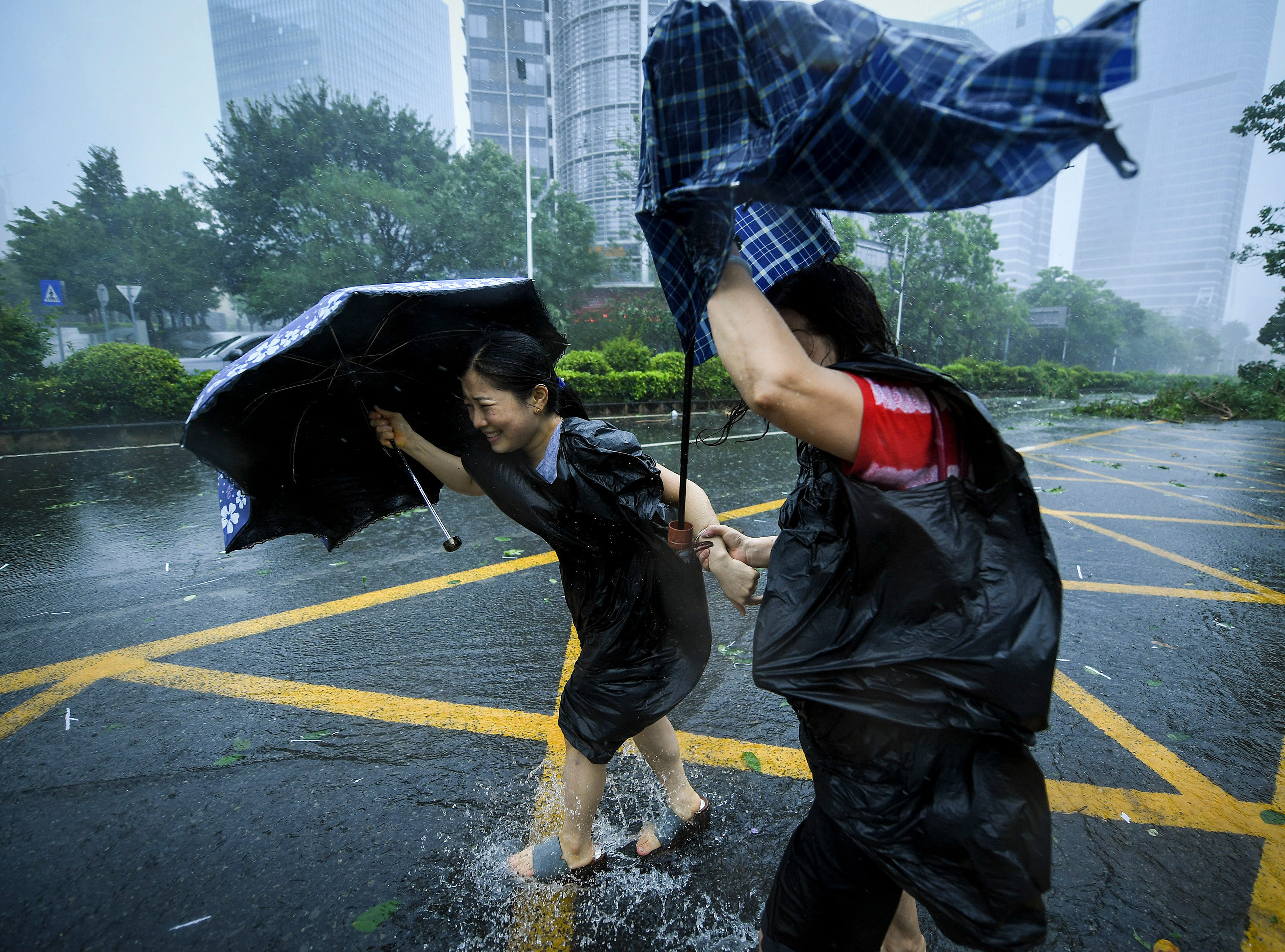 People with umbrellas walk against strong winds from Typhoon Mangkhut at Nanshan District in Shenzhen, south China's Guangdong Province, Sunday, Sept. 16, 2018.