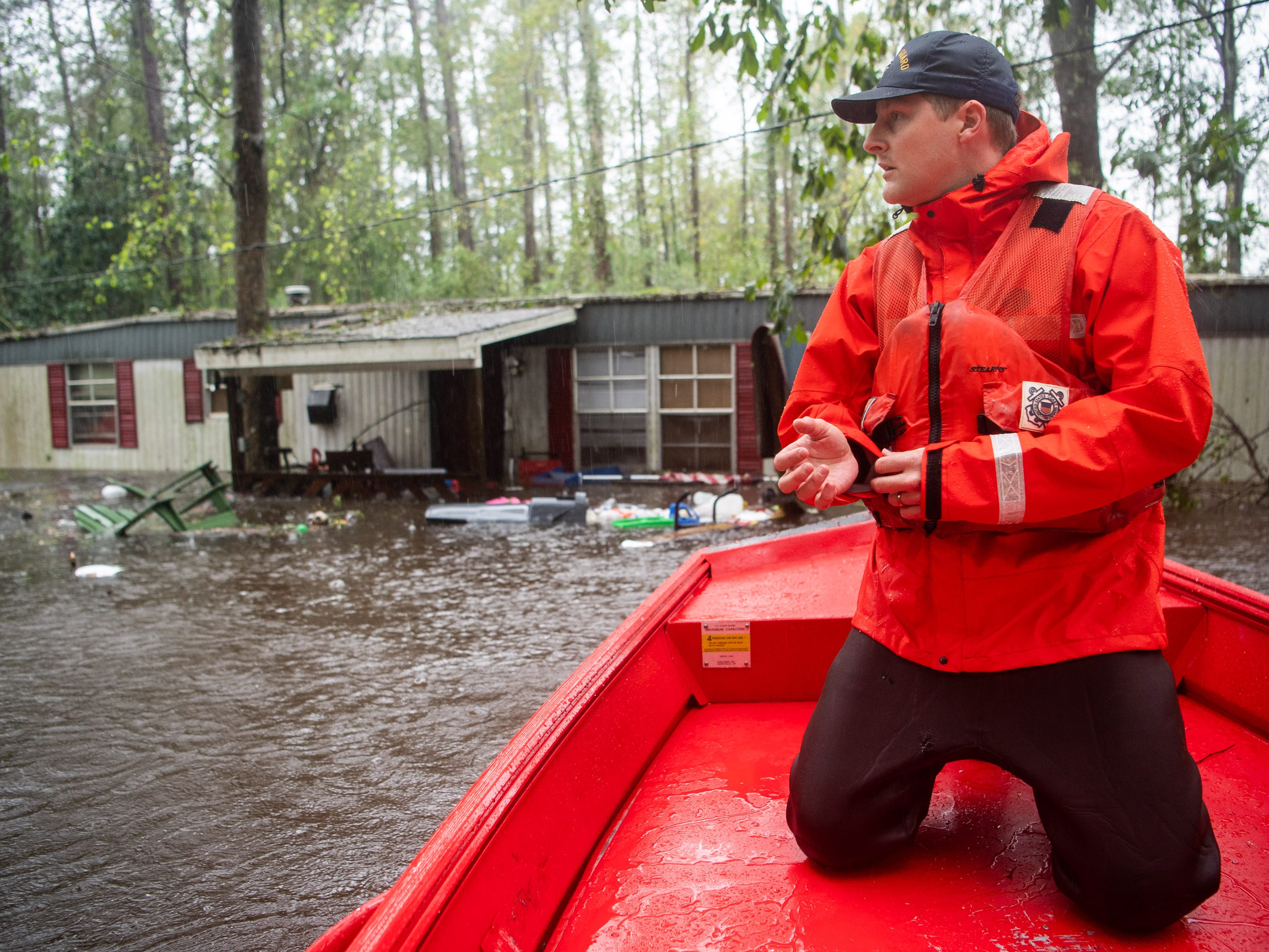 Coast Guardsman Tyler Elliott, from Louisville, Ky., surveys a flooded neighborhood in Columbus County, N.C., Sunday, Sept. 16, 2018.