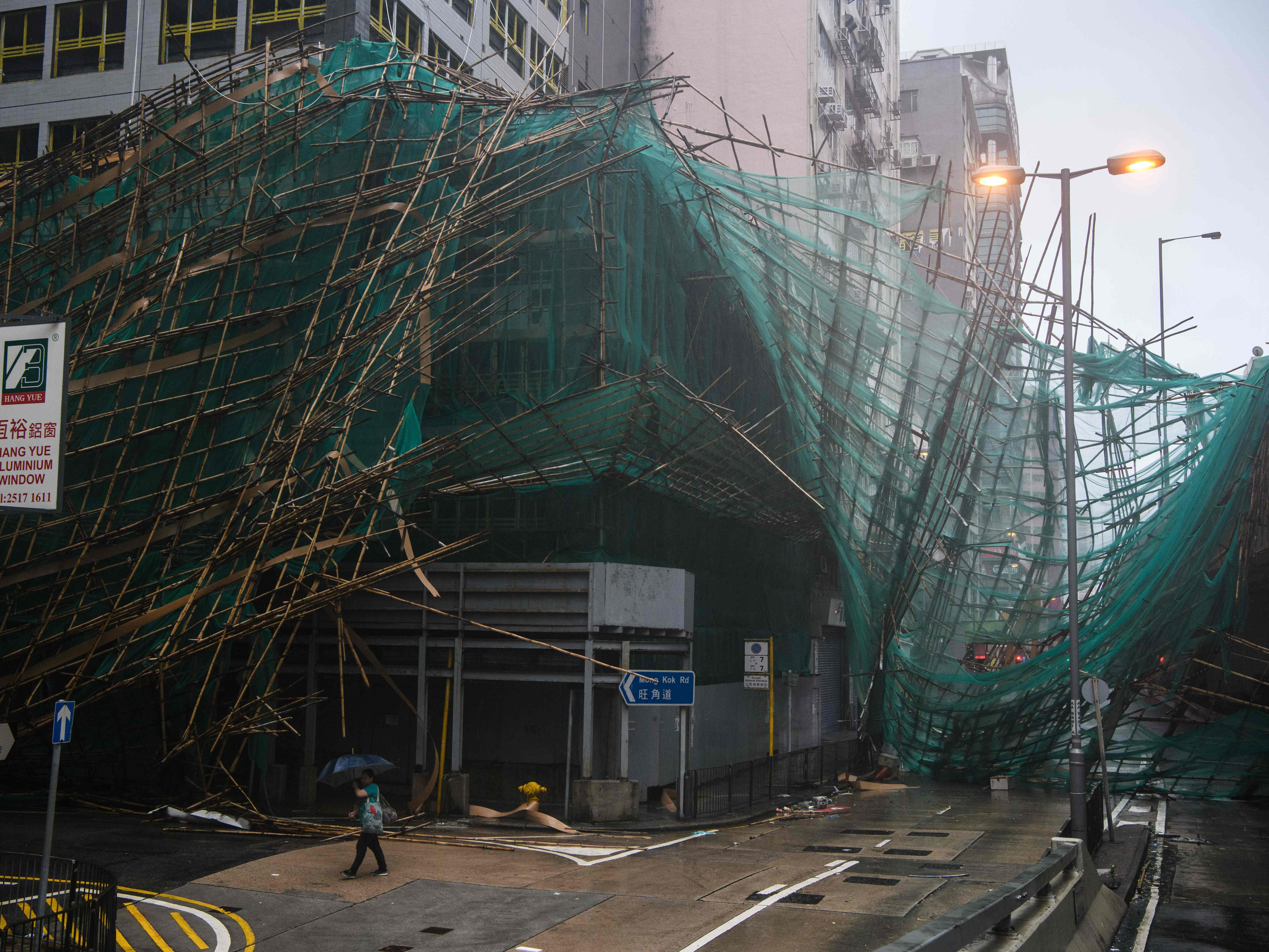 A woman uses her umbrella as she walks past collapsed bamboo scaffolding hanging from a building during Super Typhoon Mangkhut in Hong Kong on Sept. 16, 2018.