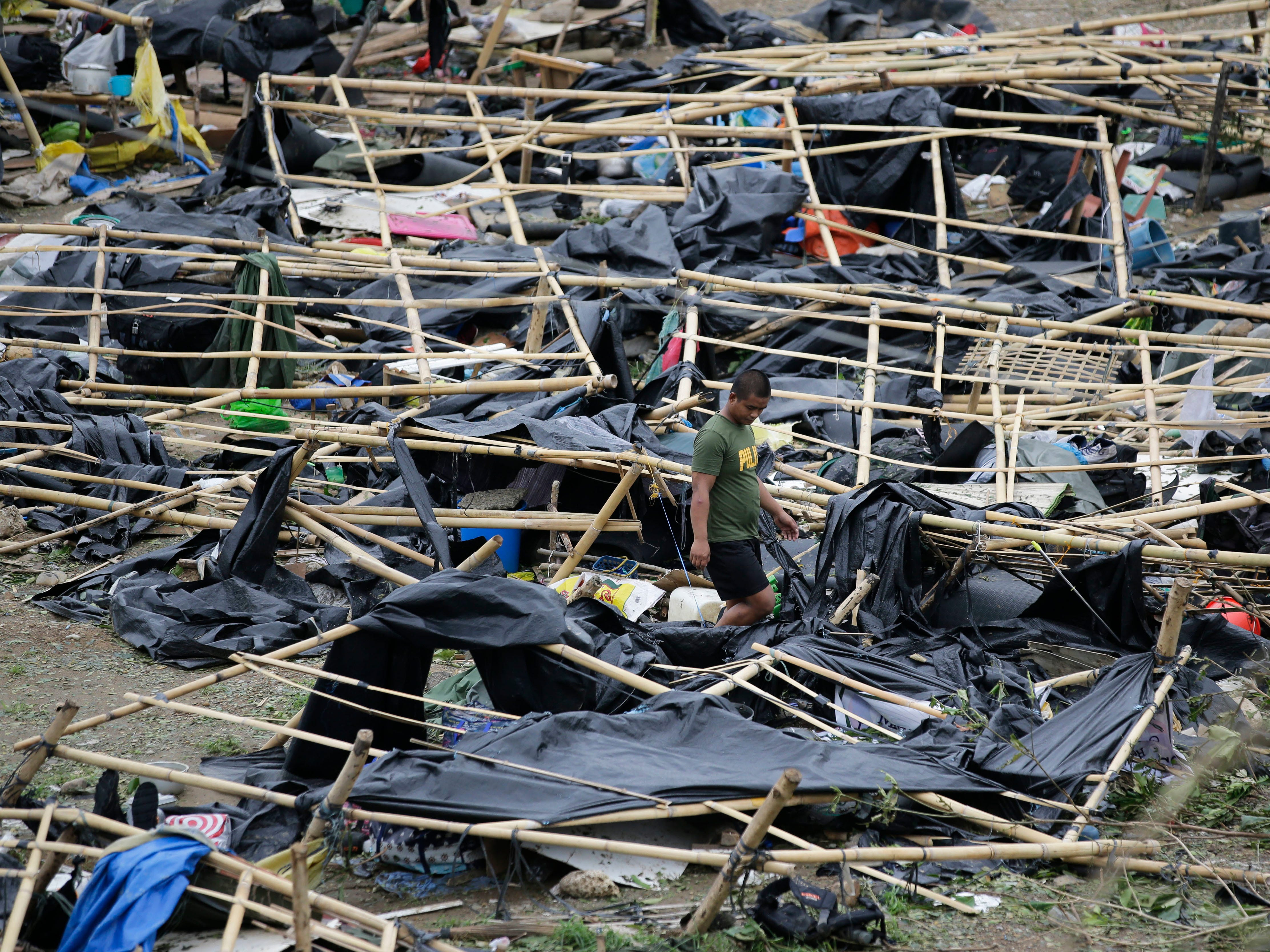 A policeman walks through makeshift tent shelters damaged by strong winds from Typhoon Mangkhut after it barreled across Tuguegarao city in Cagayan province, northeastern Philippines on Sunday, Sept. 16, 2018. Typhoon Mangkhut roared toward densely populated Hong Kong and southern China on Sunday after ravaging across the northern Philippines with ferocious winds and heavy rain causing landslides and collapsed houses.