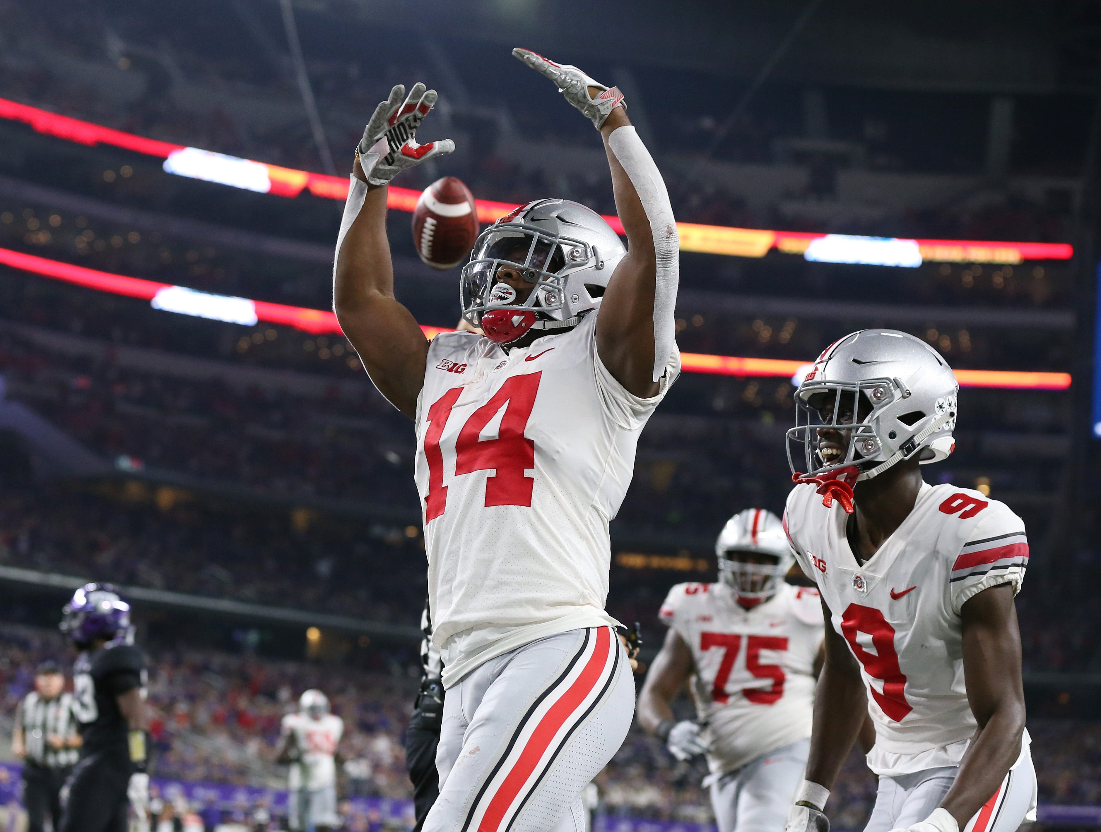 Ohio State Buckeyes halfback K.J. Hill Jr. (14) celebrates his third-quarter touchdown with receiver Binjimen Victor (9) against the Texas Christian Horned Frogs at AT&T Stadium.