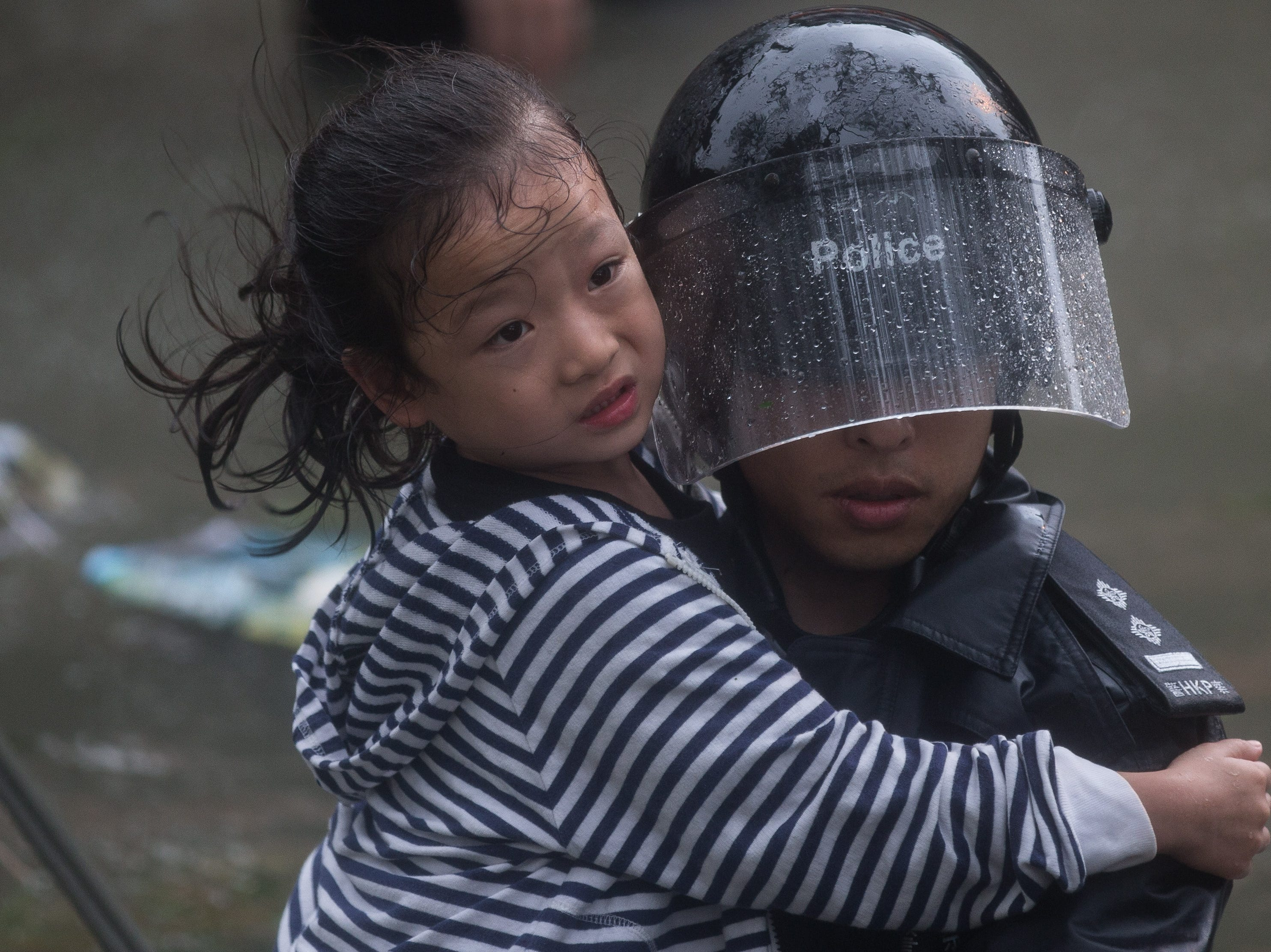 A police officer rescues a child from a flooded street during Typhoon Mangkhut in Lei Yu Mun, Hong Kong, China onSept. 16, 2018.