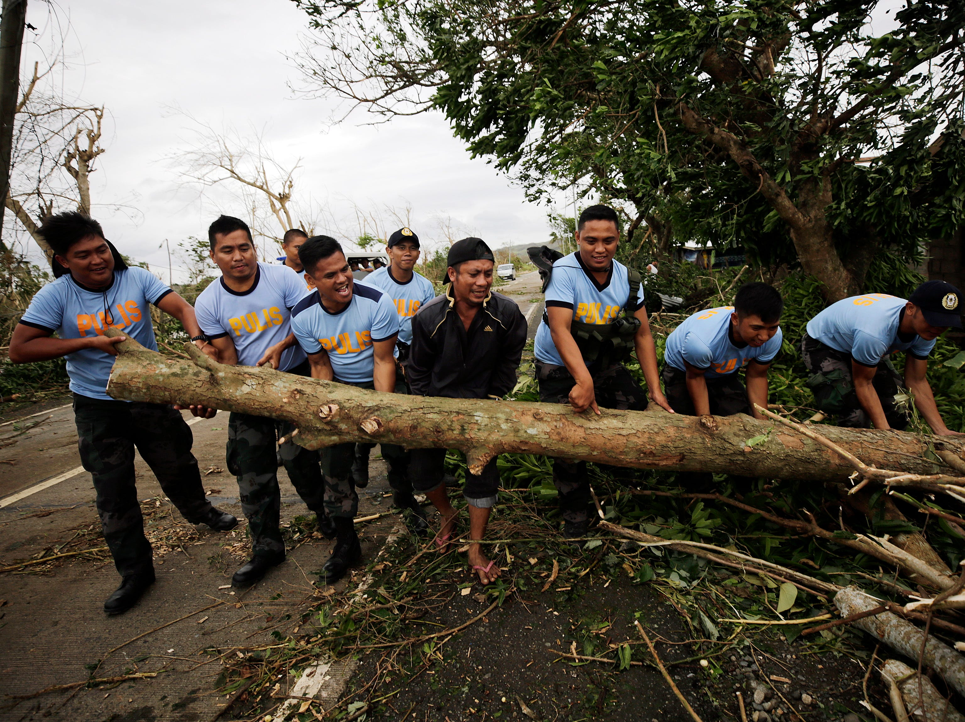 Filipino policemen clear a fallen tree in the typhoon-hit town of Caranglan, Cagayan province, Philippines on  Sept. 15, 2018.