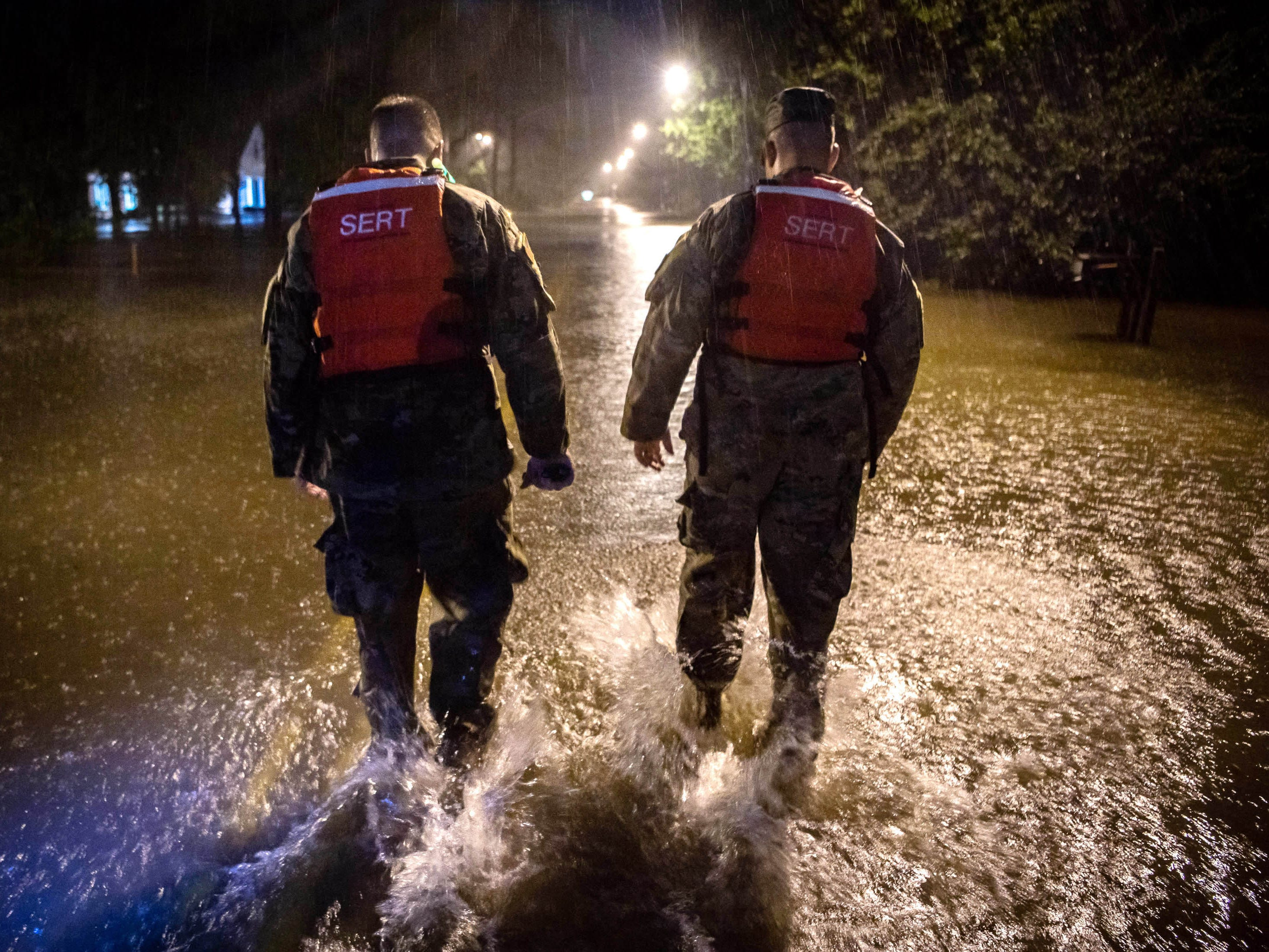 Command Sgt. Maj. Sid Baker, left, and 1st Sgt. Christopher Jones of the North Carolina National Guard patrol a flooded neighborhood as rain from tropical storm Florence continues to fall on Lumberton, N.C., on Sept. 15, 2018.