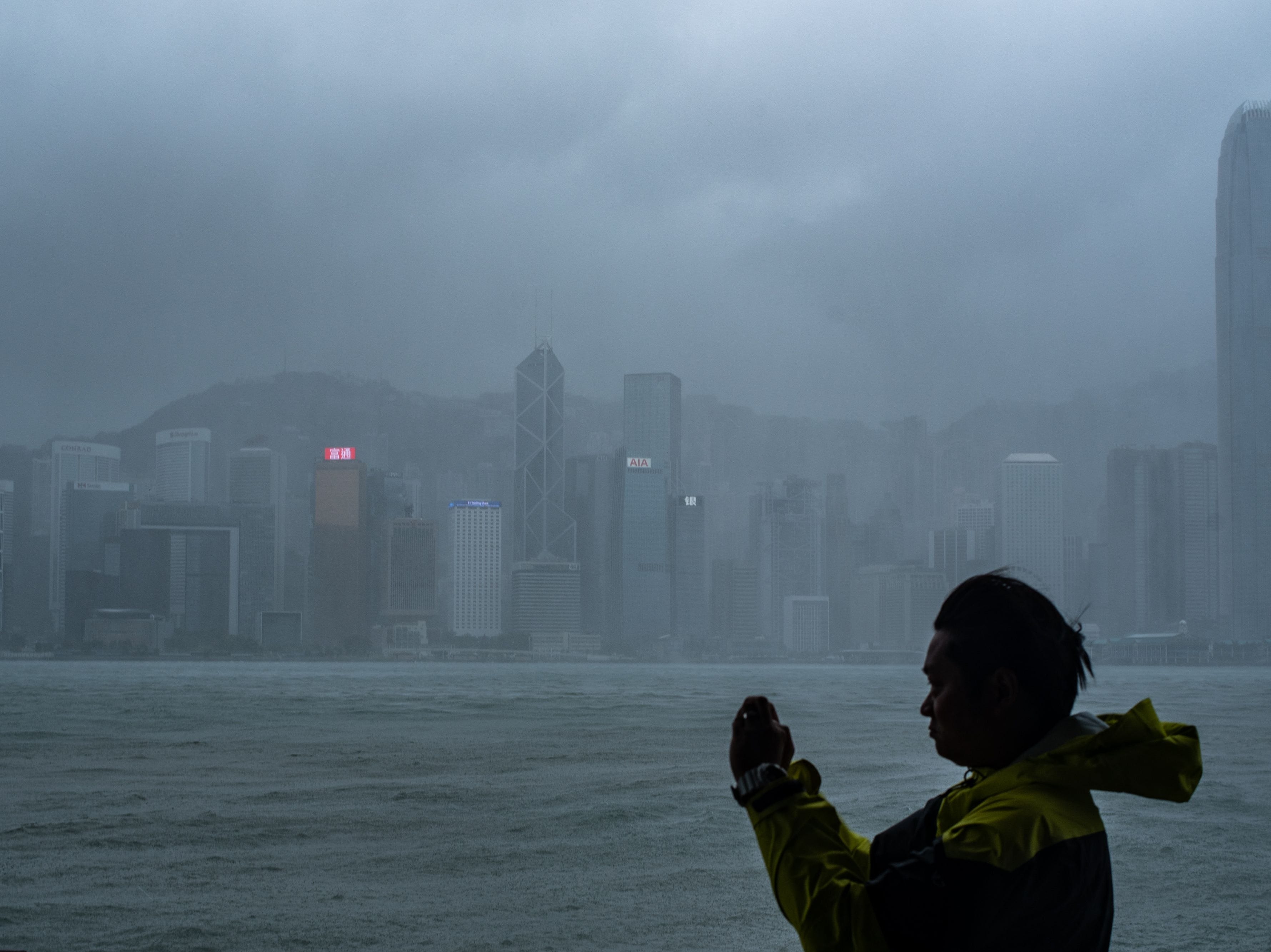 A man takes photos during the approach of super Typhoon Mangkhut to Hong Kong on Sept. 16, 2018. Super Typhoon Mangkhut has smashed through the Philippines, as the biggest storm to hit the region this year claimed the lives of its first victims and forced tens of thousands to flee their homes.