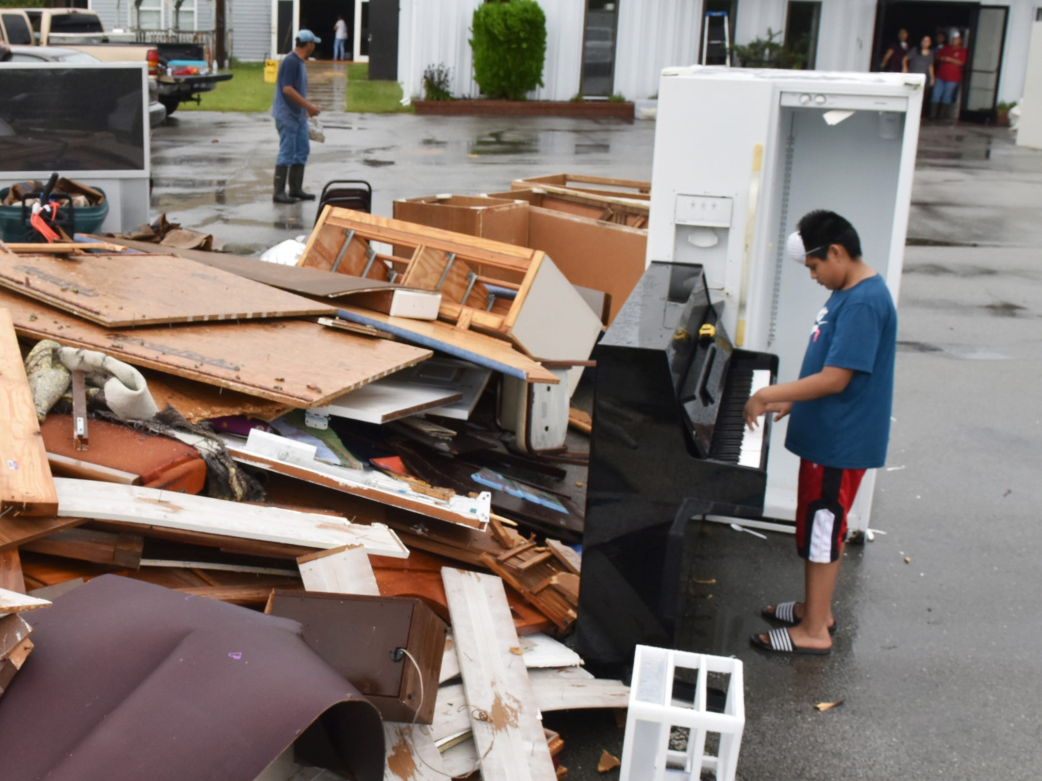 Manuel Osirio, 12, of Moorehead City, N.C., plays a piano among the pile of water soaked items being thrown out at the Seventh-Day Adventist Church in New Bern, N.C., Sunday, Sept. 16, 2018.