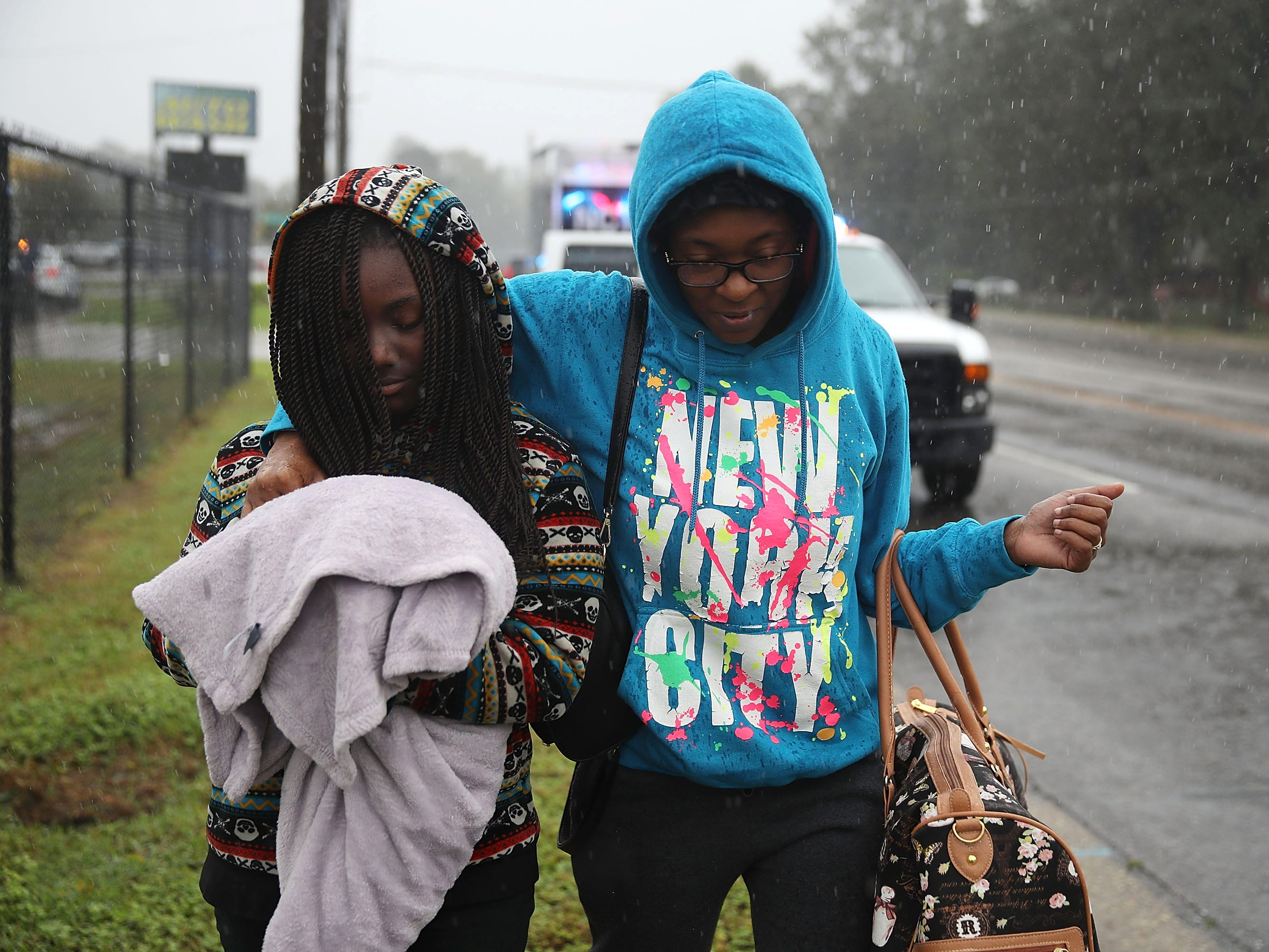 Naiya Willis, left, and Candice Willis walk to an evacuation bus as they leave their home ahead of possible flooding after Hurricane Florence passed through the area on Sept. 16, 2018 in Fayetteville, N.C.