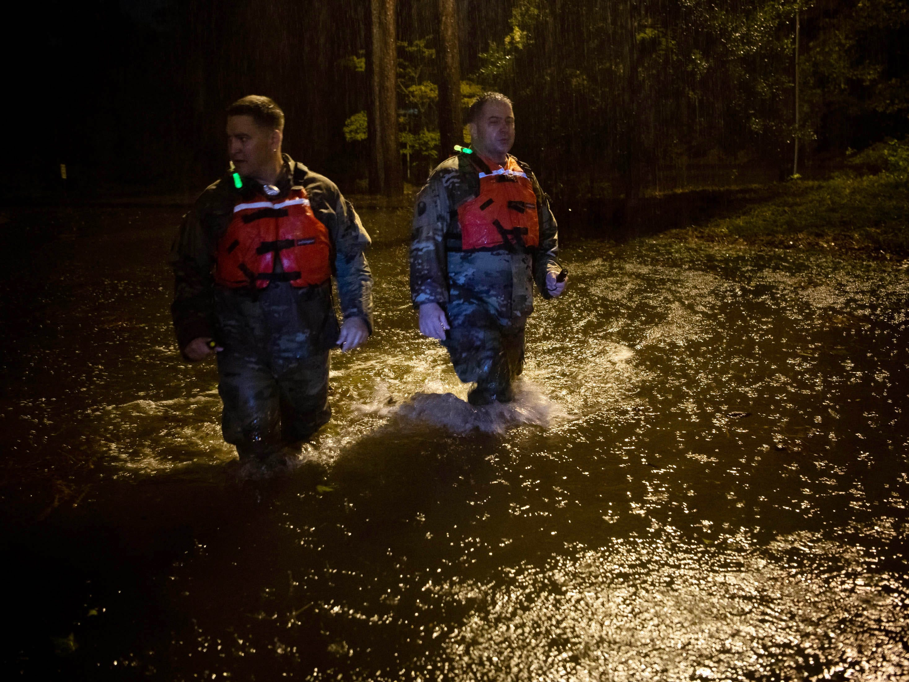 First Sgt. Christopher Jones, left, and Command Sgt. Maj. Sid Baker, right, of the North Carolina National Guard patrol a flooded neighborhood as rain from tropical storm Florence continues to fall on Lumberton, N.C. on Sept. 15, 2018.