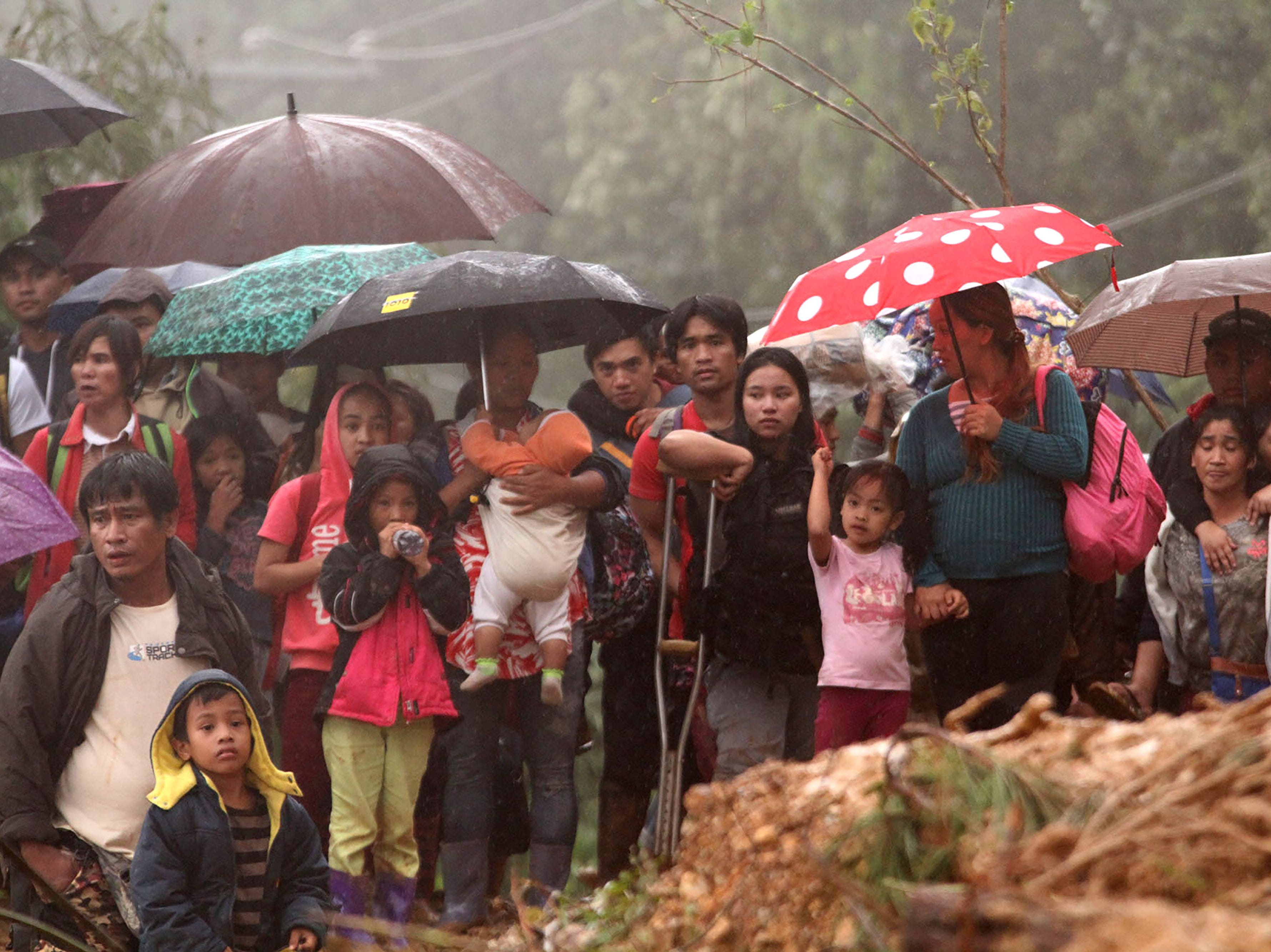 Families and relatives of miners move to safer grounds after massive landslides triggered by Super Typhoon Mangkhut in Itogon town, Benguet province on Sept. 16, 2018.