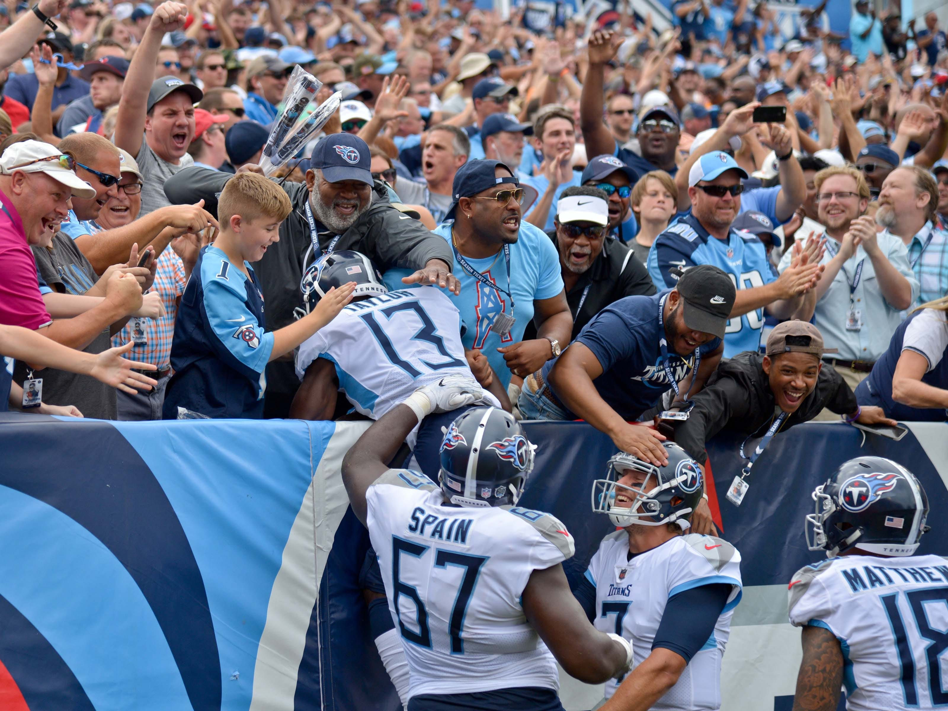 Tennessee Titans wide receiver Taywan Taylor celebrates with teammates Titans offensive guard Quinton Spain and quarterback Blaine Gabbert and wide receiver Rishard Matthews and fans after scoring a touchdown against the Houston Texans during the first half at Nissan Stadium.