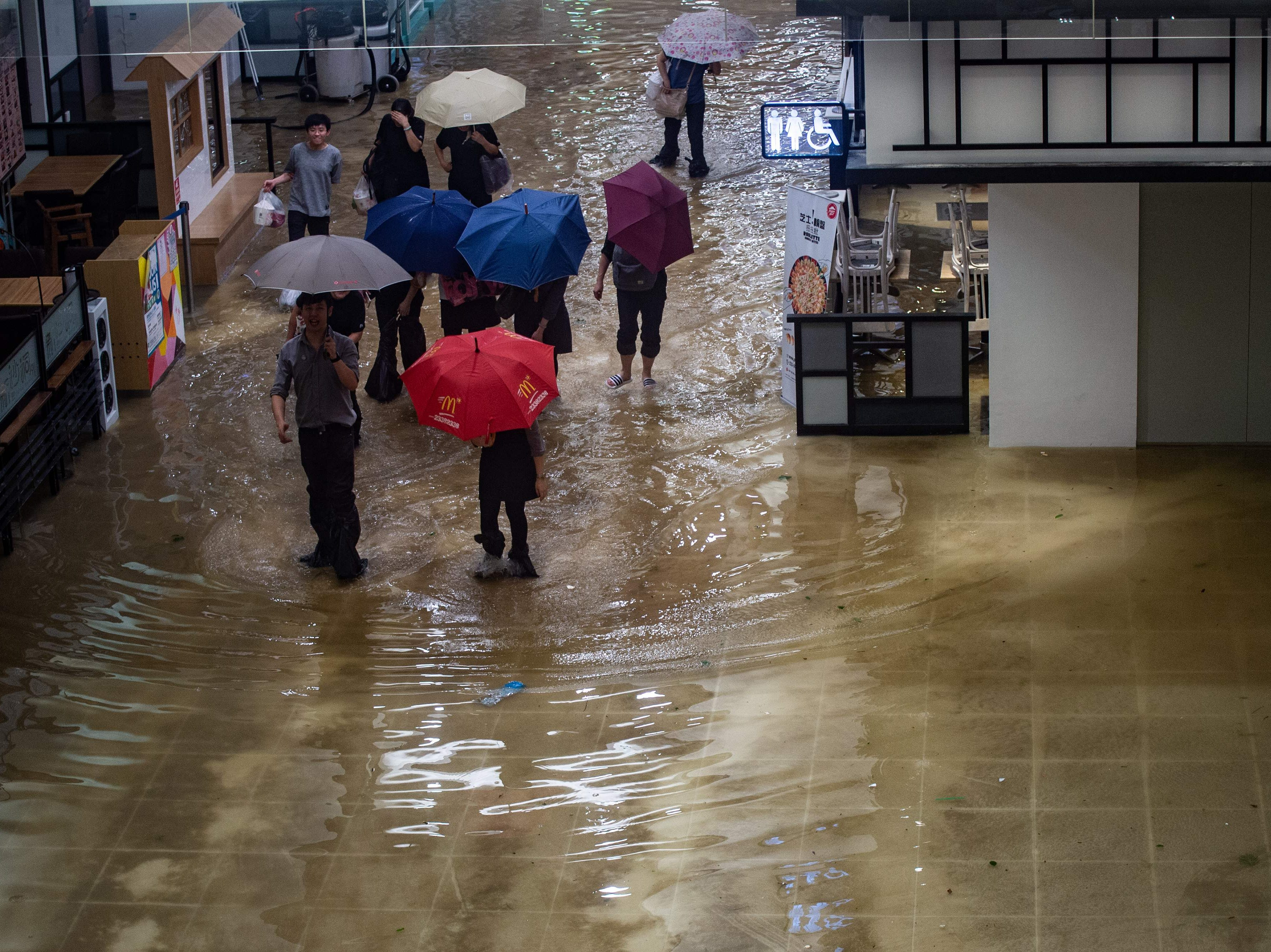 People walk through a flooded shopping mall in Heng Fa Chuen district during Super Typhoon Mangkhut in Hong Kong on Sept. 16, 2018.