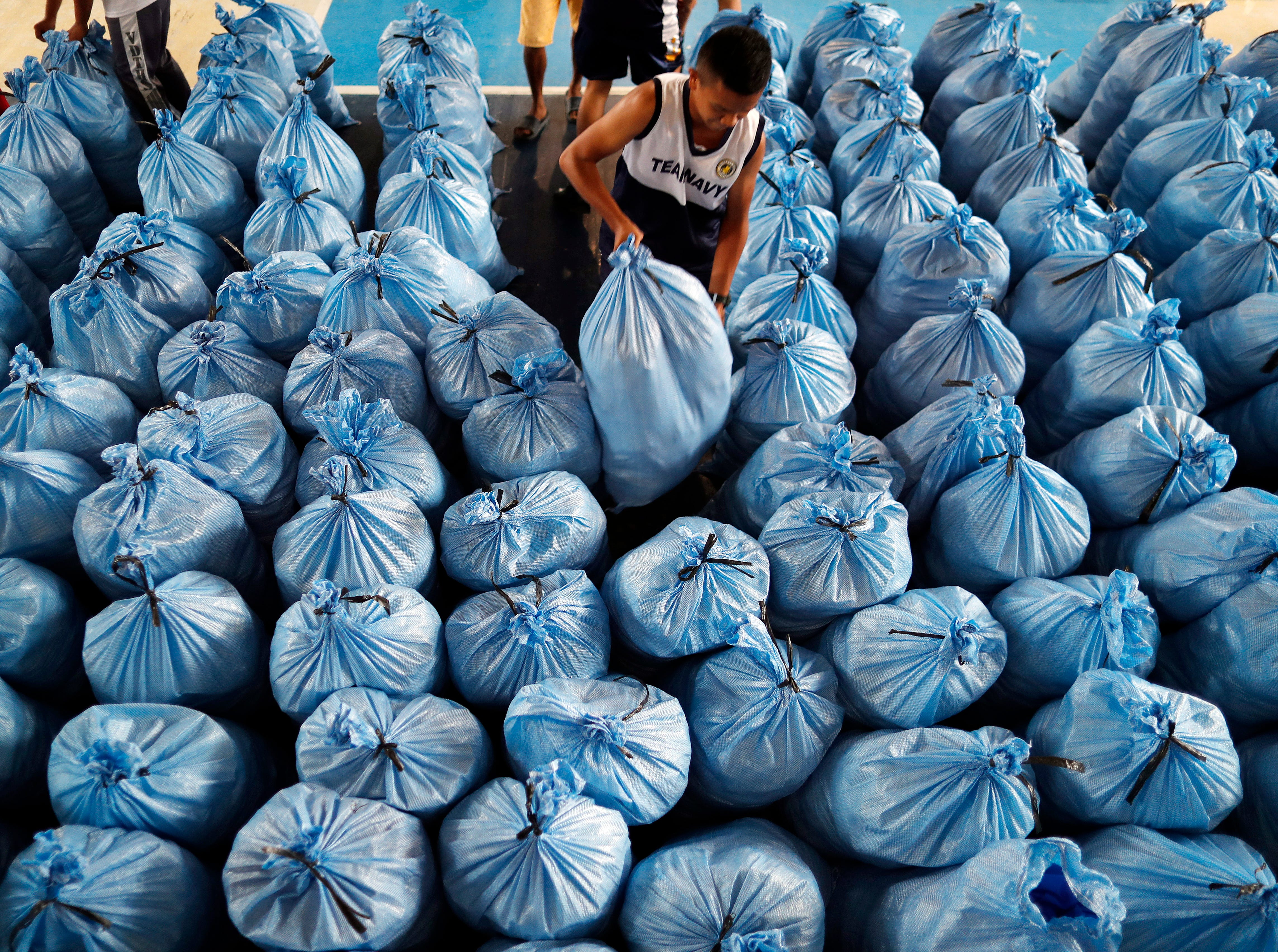 Filipino navy personnel carries a sack of relief goods in the typhoon-hit city of Tuguegarao, Cagayan province, Philippines on Sept. 16, 2018.