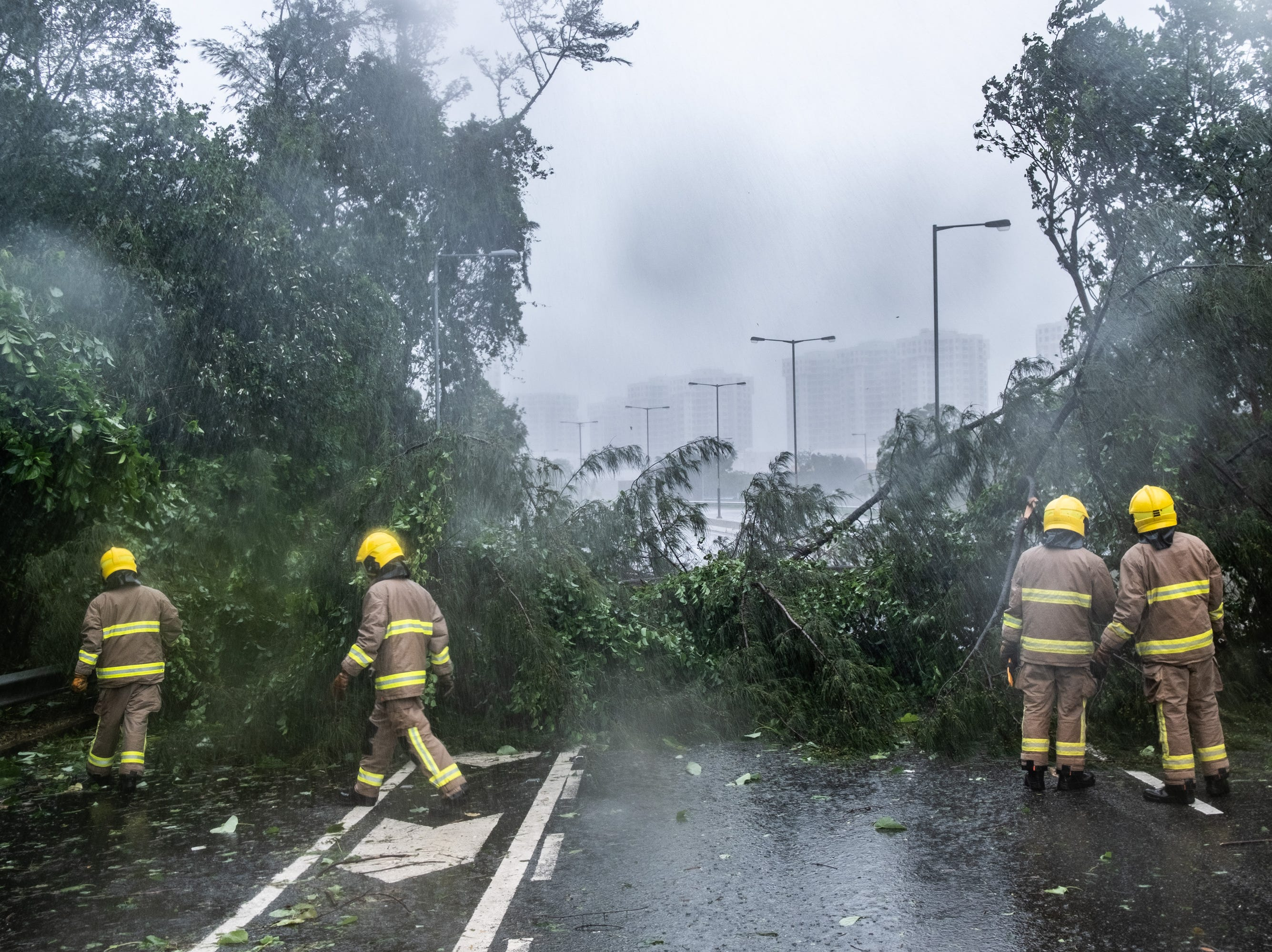 Firefighters remove the debris on the road on Sept. 16, 2018 in Hong Kong.