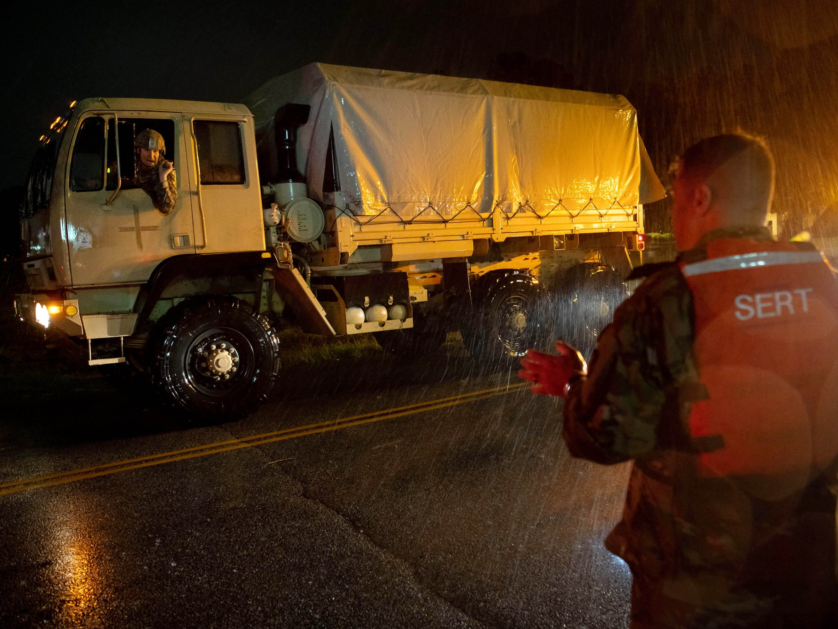 Command Sgt. Maj. Sid Baker, right, of the North Carolina National Guard, speaks with the driver of a National Guard truck carrying evacuees from a flooded neighborhood as rain from tropical storm Florence continues to fall on Lumberton, N.C. on Sept. 15, 2018.