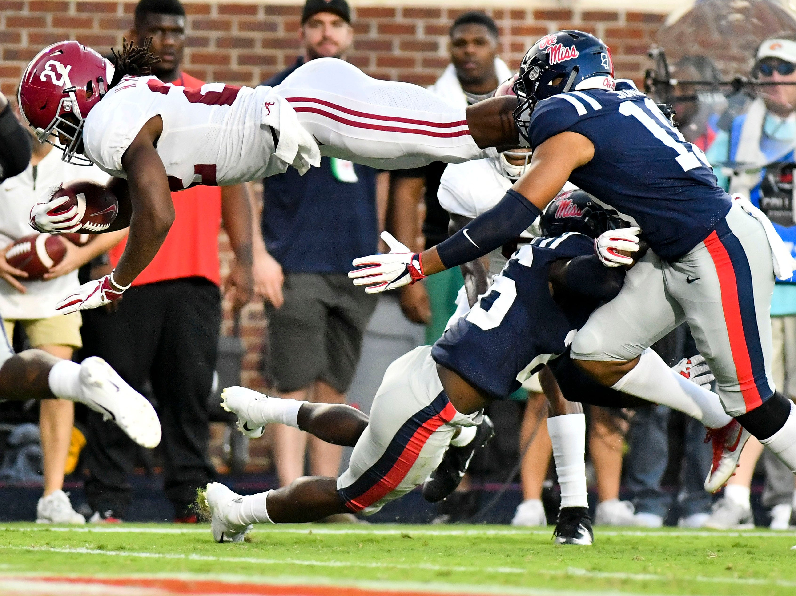 Alabama Crimson Tide running back Najee Harris (22) dives over Mississippi Rebels defensive back Jalen Julius (26) and linebacker Jacquez Jones (10) for a touchdown during the first quarter at Vaught-Hemingway Stadium.