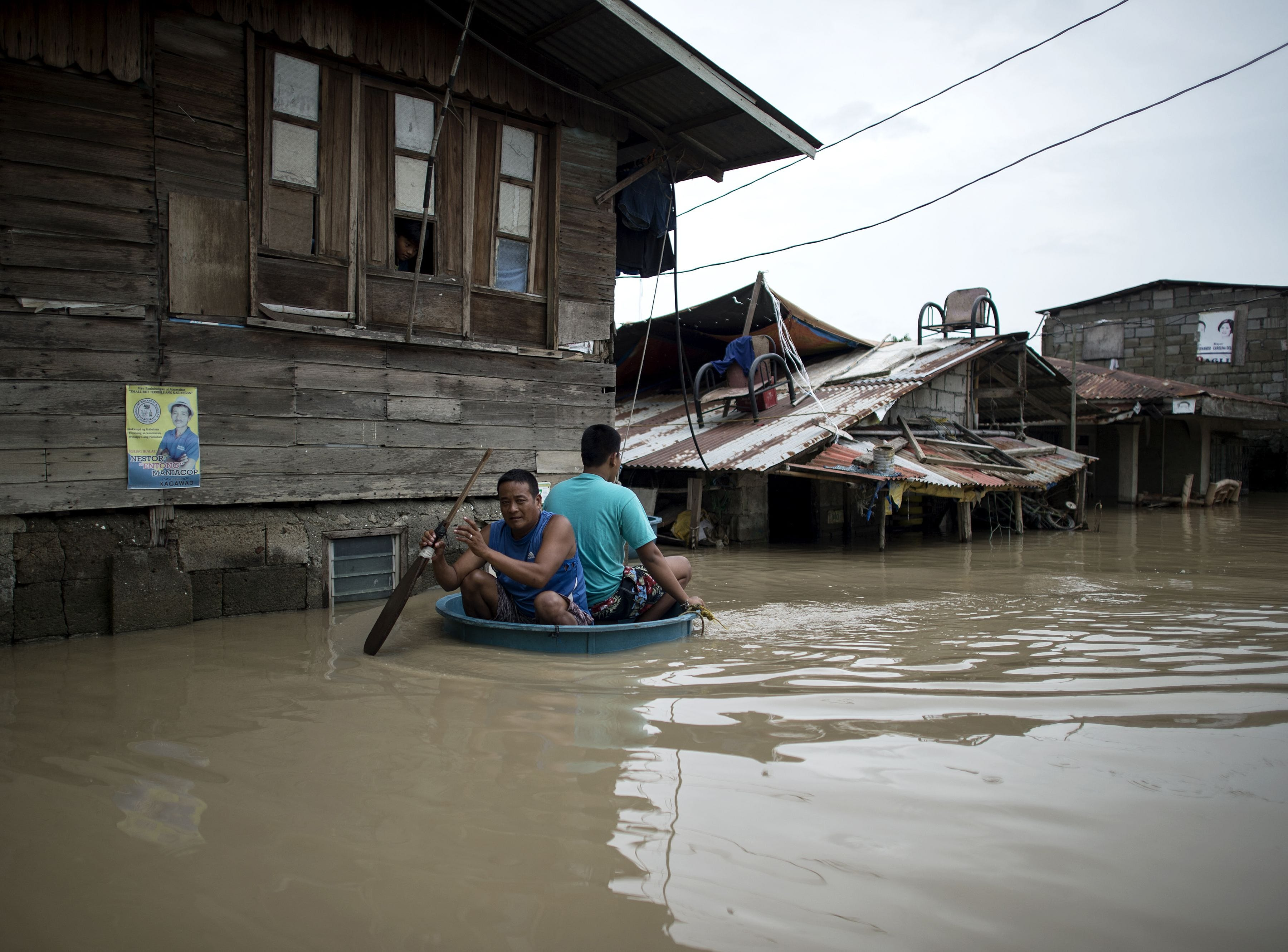 Men use a basin to cross a flooded street in the aftermath of Super Typhoon Mangkhut at Salonga Compound in Calumpit, Bulacan on Sept. 16, 2018.