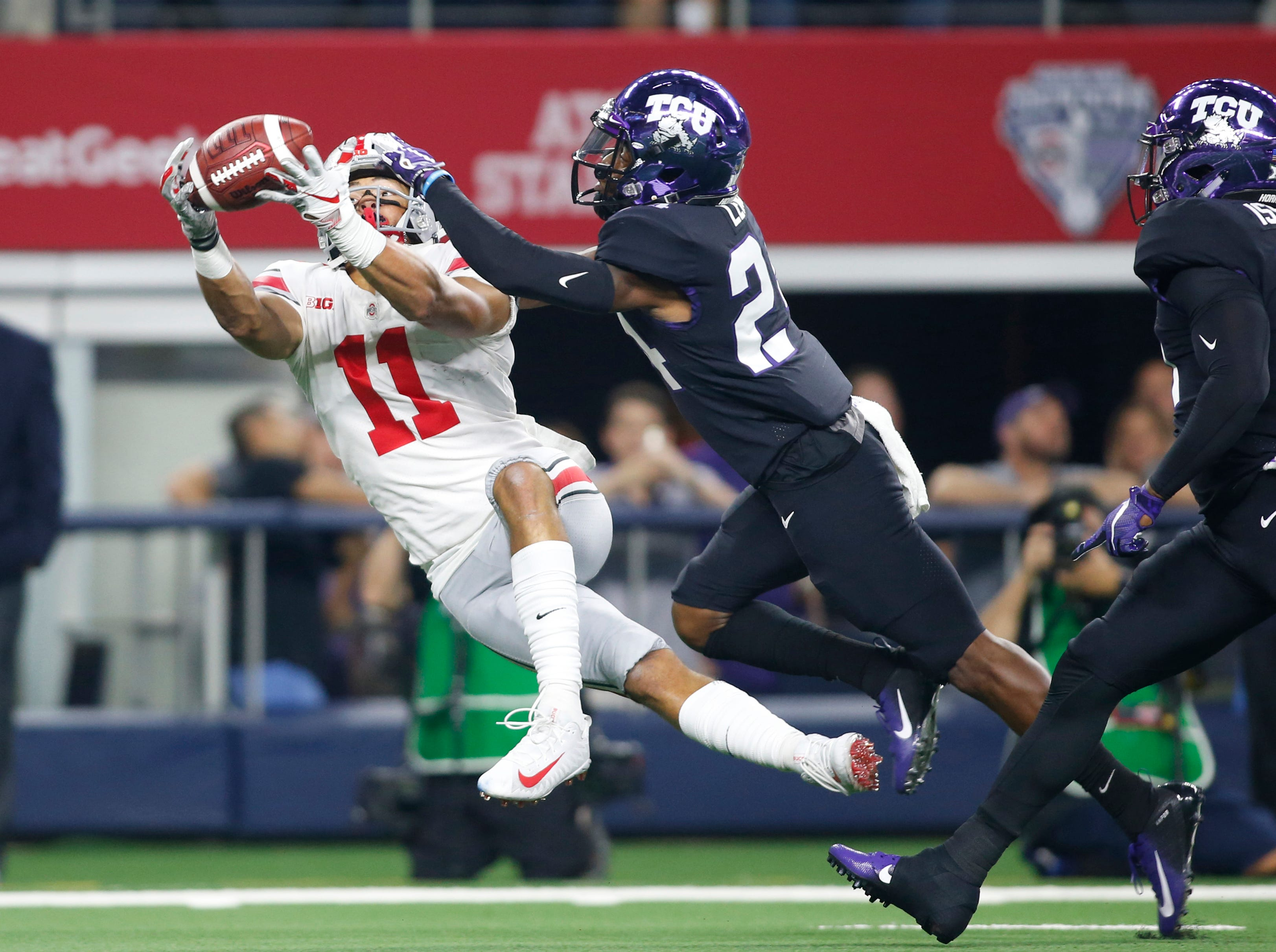 Ohio State Buckeyes wide receiver Austin Mack (11) catches a pass against TCU Horned Frogs cornerback Julius Lewis (24) in the first quarter at AT&T Stadium.