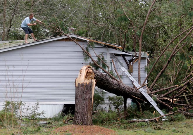 Chris Lishka works to remove a tree from his roof after Hurricane Florence hit Emerald Isle N.C.,Sunday, Sept. 16, 2018.