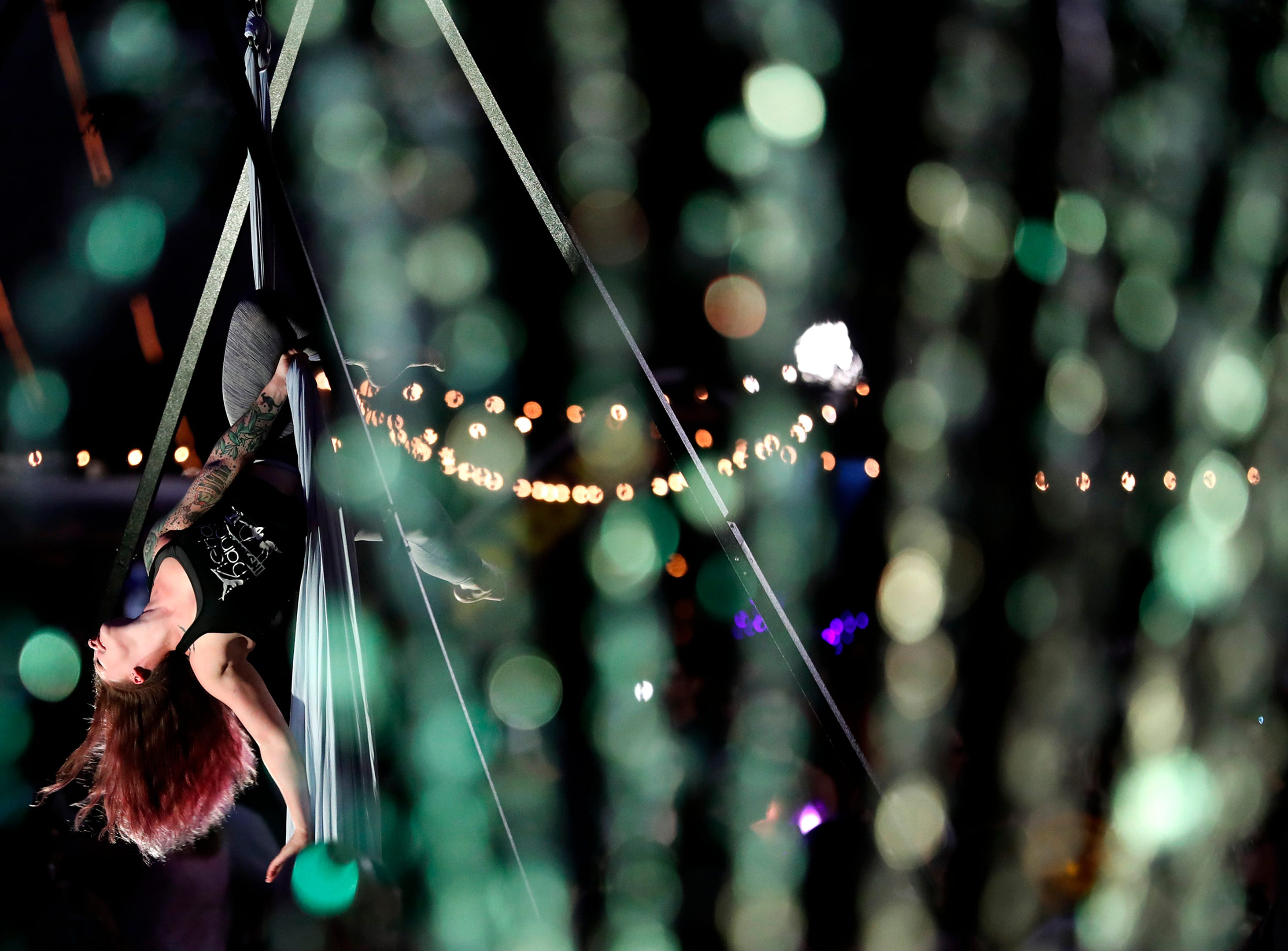 A fountain in downtown Menasha is lit with green light as Olivia Oswalt, an instructor with Aerial Dance, performs during Bazaar After Dark Wednesday, Sept. 12, 2018, in Menasha, Wis.Danny Damiani/USA TODAY NETWORK-Wisconsin