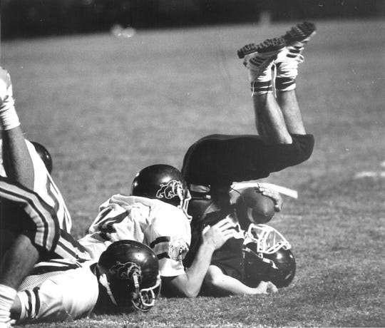 A pair of Wylie defenders upend a Merkel ball carrier during a game in the 1990s.