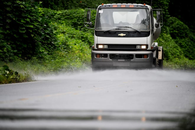Adrian Edwards drives a city flusher truck on Azalea Road to remove debris Sept. 17, 2018 in East Asheville following flooding from Swannanoa River after Tropical Storm Florence.