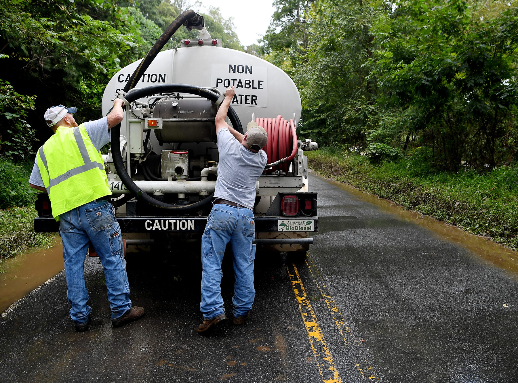 Jonathan Surrett, left, and Adrian Edwards replace a hose after filling up a city flusher truck to clean Azalea Road of debris in East Asheville Sept. 17, 2018 following flooding from Swannanoa River after Tropical Storm Florence.