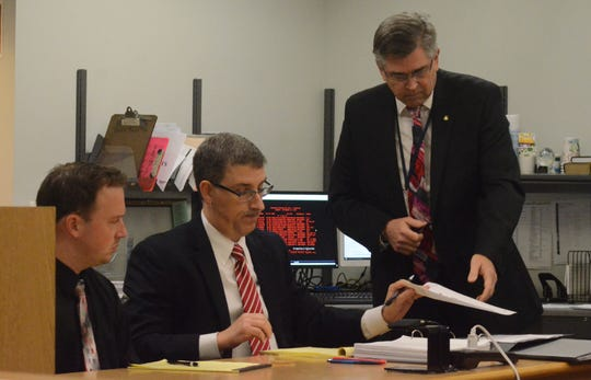 Tyler Millward, from left,  watches as defense attorney Anastase Markou and Prosecutor David Gilbert review evidence.
