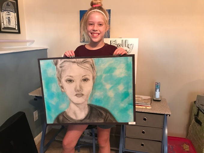 Johnson City Central School District seventh grader Molly Jablonowski, 12, holds a self-portrait next to her drawing studio.