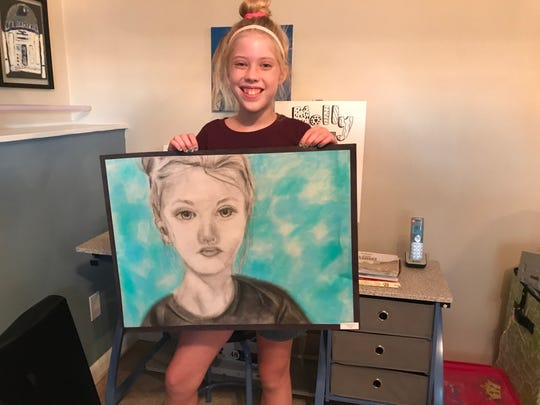 Johnson City Central School District seventh-grader Molly Jablonowski, 12, holds a self-portrait next to her drawing studio.